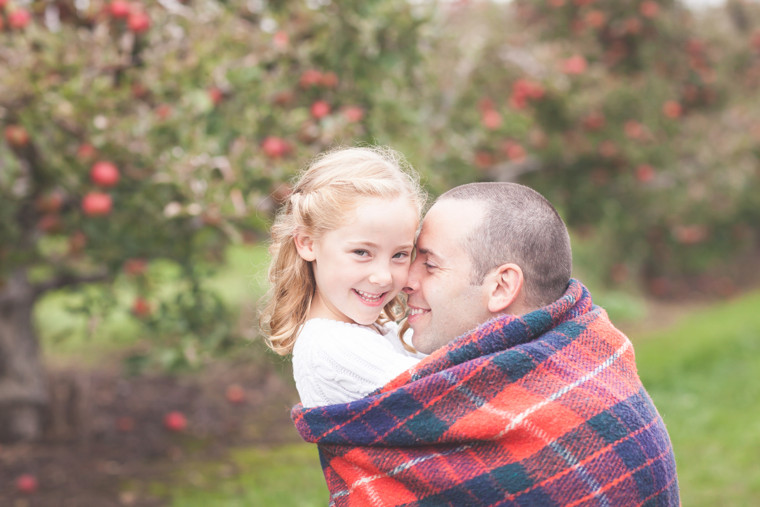 Father hugging daughter at the apple orchard