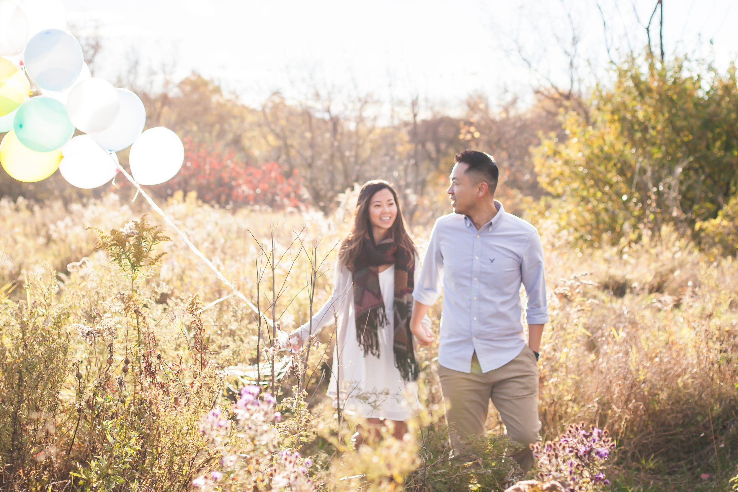 Outdoor engagement session on a field with pastel balloons