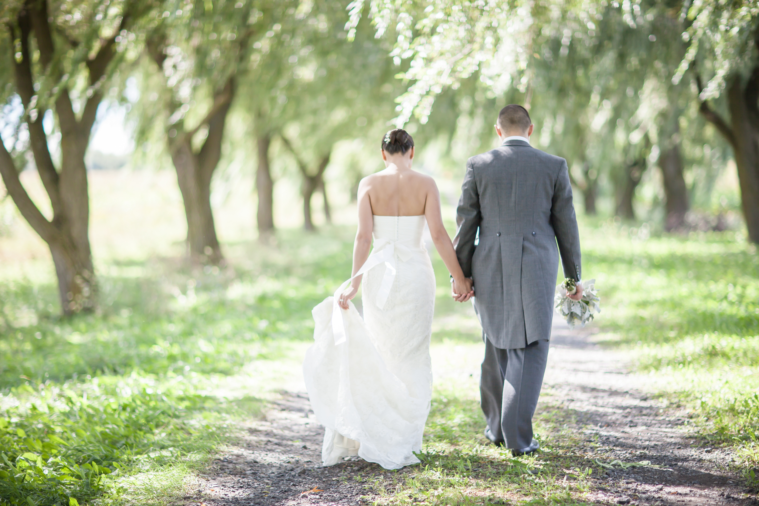 Bride and groom walking through a willow tree farm