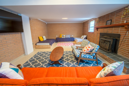Cosmic Lounge - The Cosmic Lounge has three twin beds, lounge area, ping pong table, private outdoor access, and a TV. Located in the walkout basement of the Swamp Rabbit Lodge. Hall bathrooms upstairs. Access to community kitchen, outdoor decks and hot tub. Starts at $80/night.