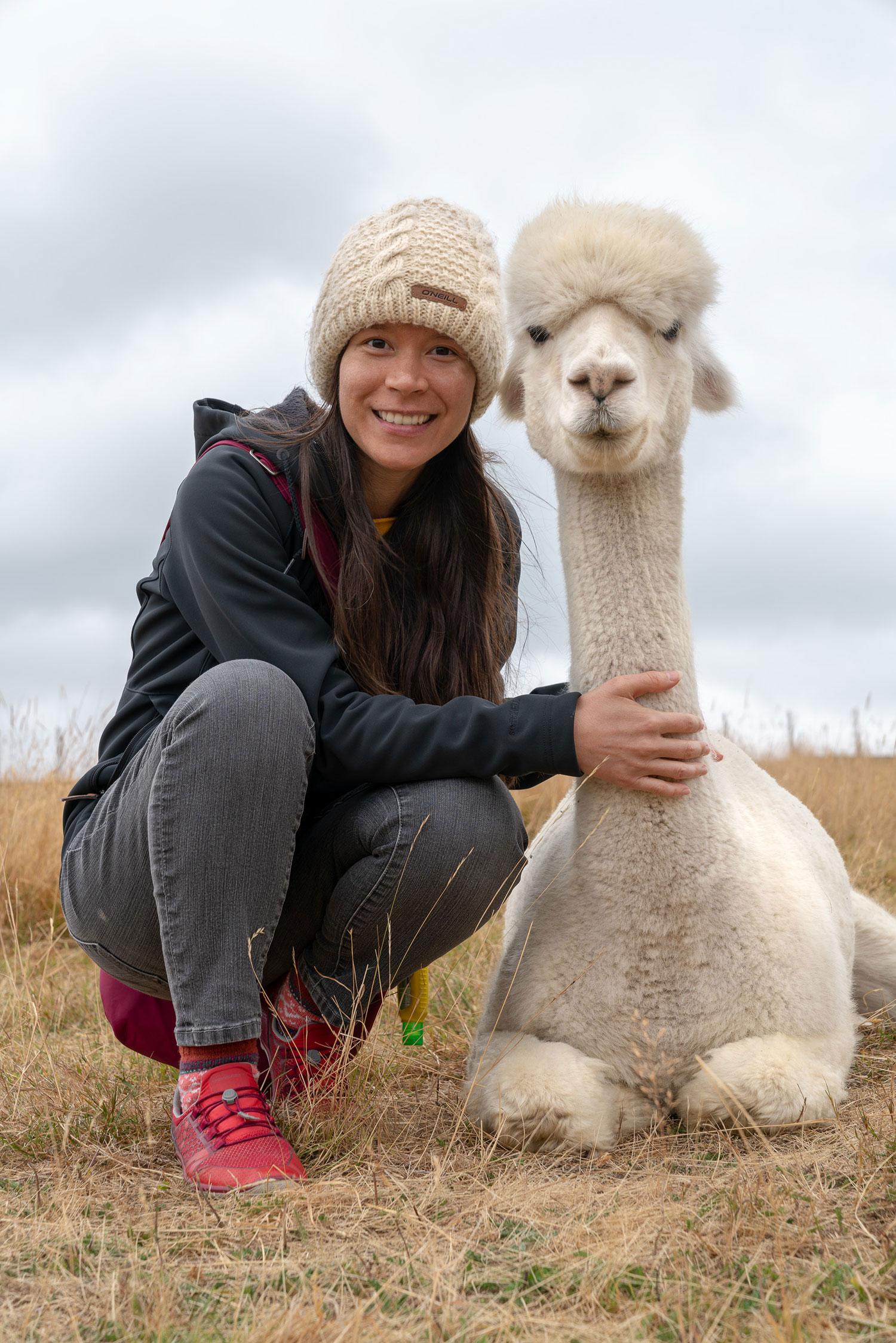 Thaneeya McArdle with an alpaca at Shamarra Alpaca Farm in Akaroa, New Zealand