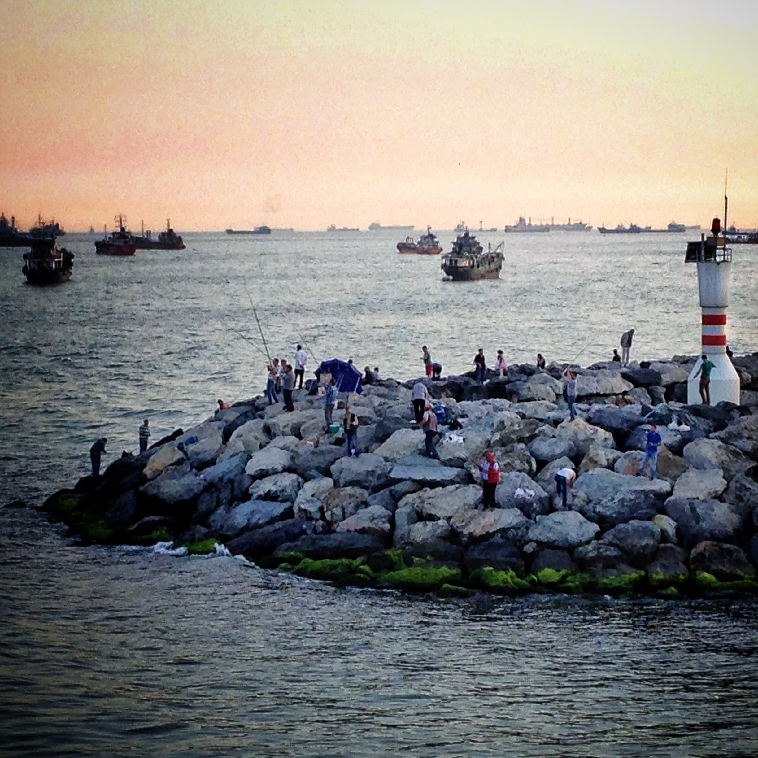 """Istanbullu's fishing off Yenikapi against the backdrop of international commercial liners awaiting permission to traverse the narrow Bosphorus Strait. Locals jokingly refer to the Sea of Marmara as the """"parking lot."""""""