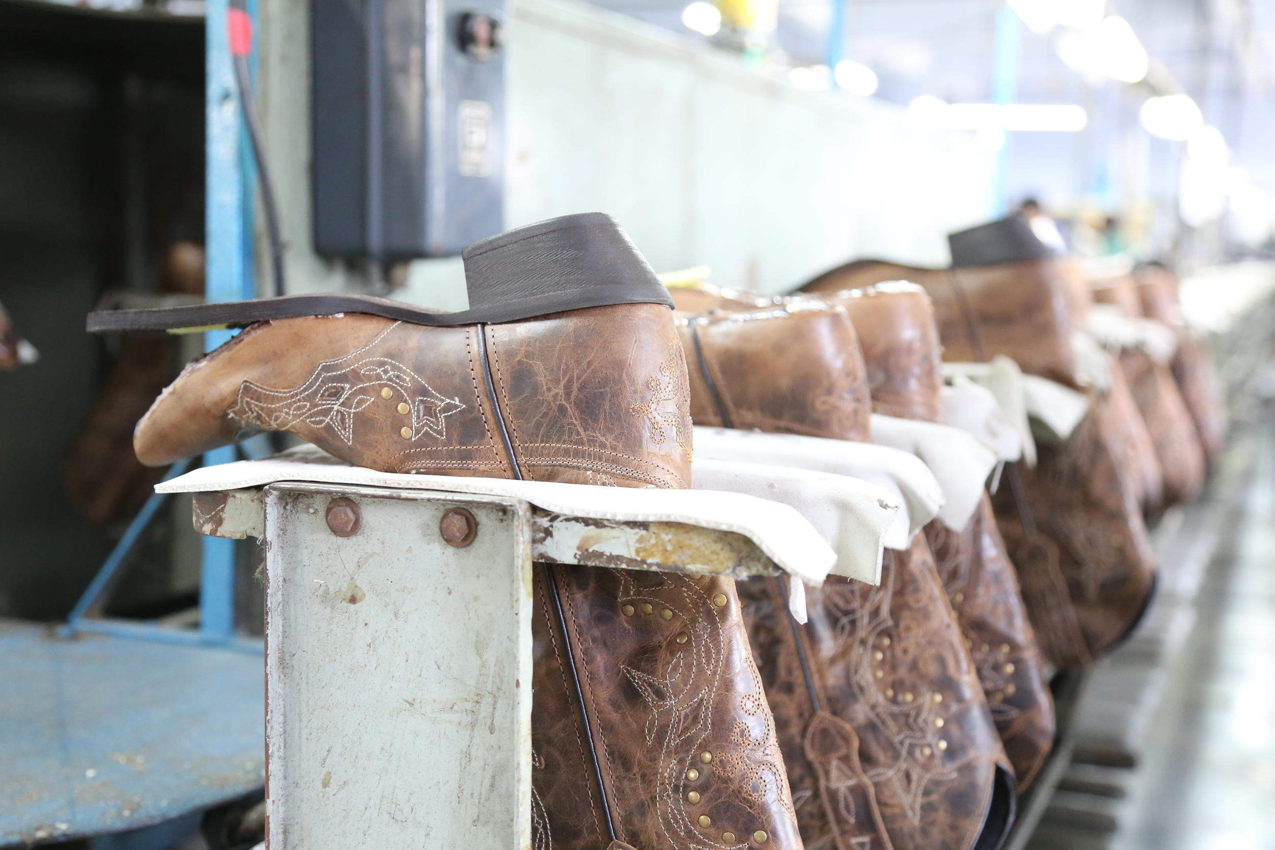 Cowboy boots on assembly line ready for sole pasting