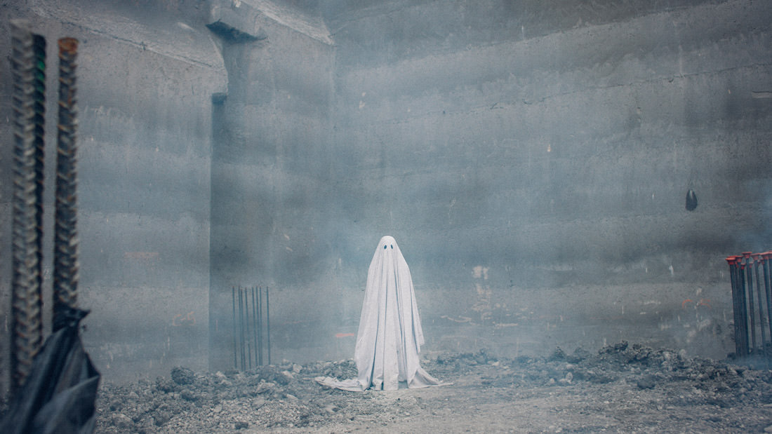 Lowery's meticulously sparse narrative contemplates a spectral figure who was once a man (Casey Affleck). Prematurely taken from this Earth, he makes his way toward his former home, where he is fated to remain forevermore. Shrouded in a white sheet, he observes the lament of his grief-stricken lover (Rooney Mara). Bearing unseen witness to her pain, the wisp stands sentry for years to come, interacting only with time as it hurtles further and further forward, the remnants of his humanity quietly evaporating.