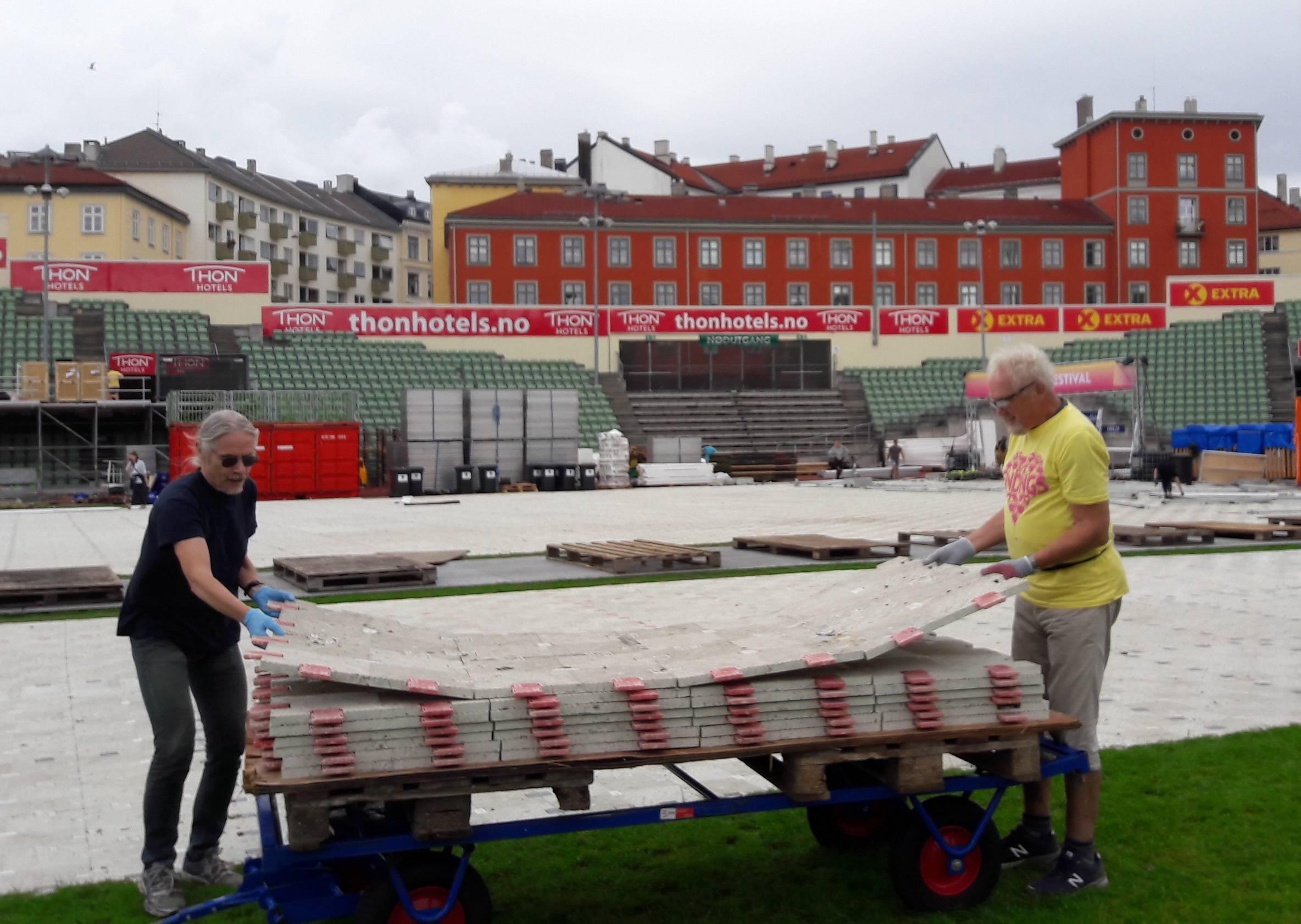 """Stein Opdahl og Sven-Åge Svensson stabler gulvplater. Det ligger fortsatt """"noen"""" igjen i bakgrunnen. (Foto: Petter Andersen)"""