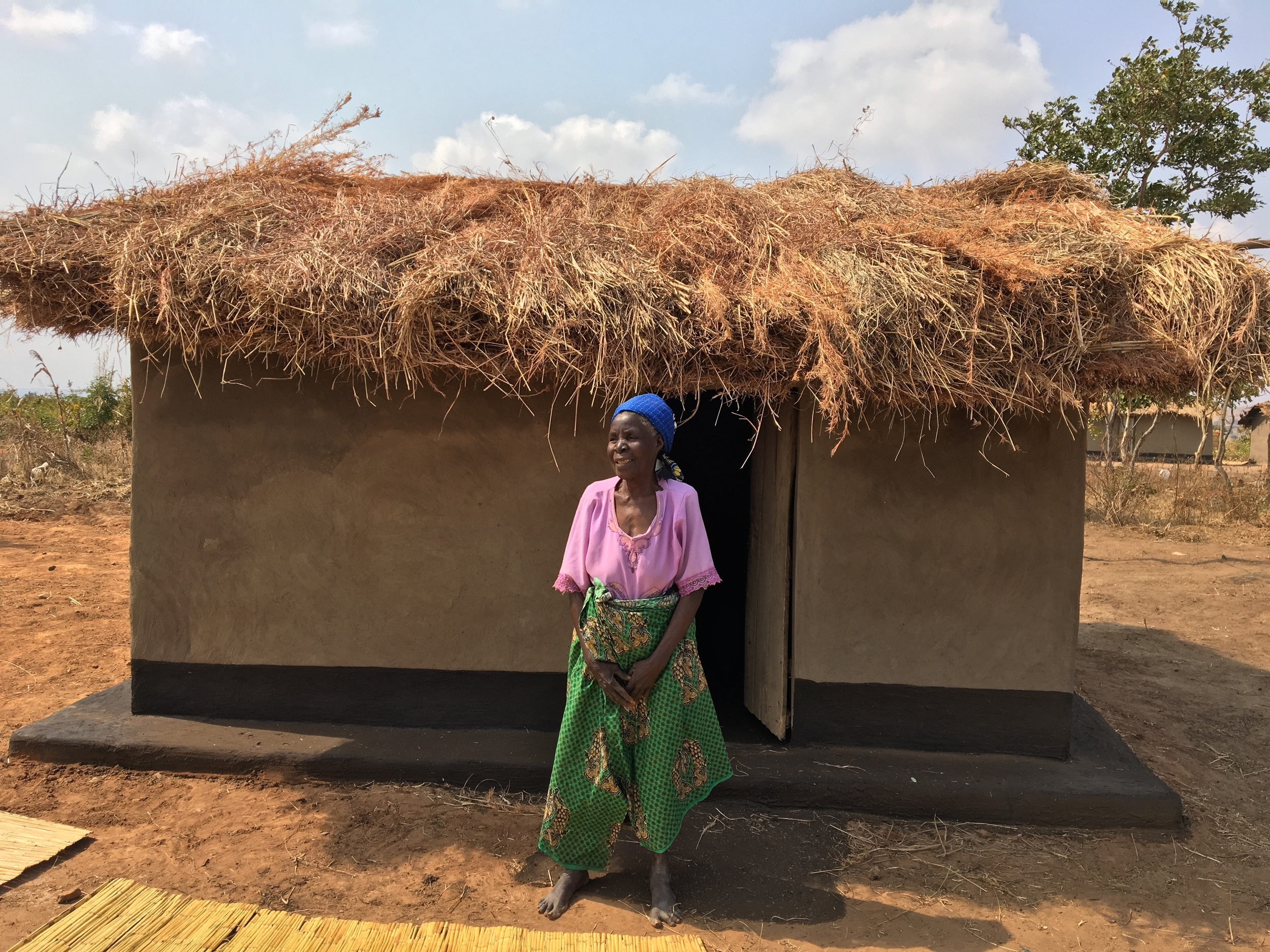 Elizabeth in front of her new home built by World Relief