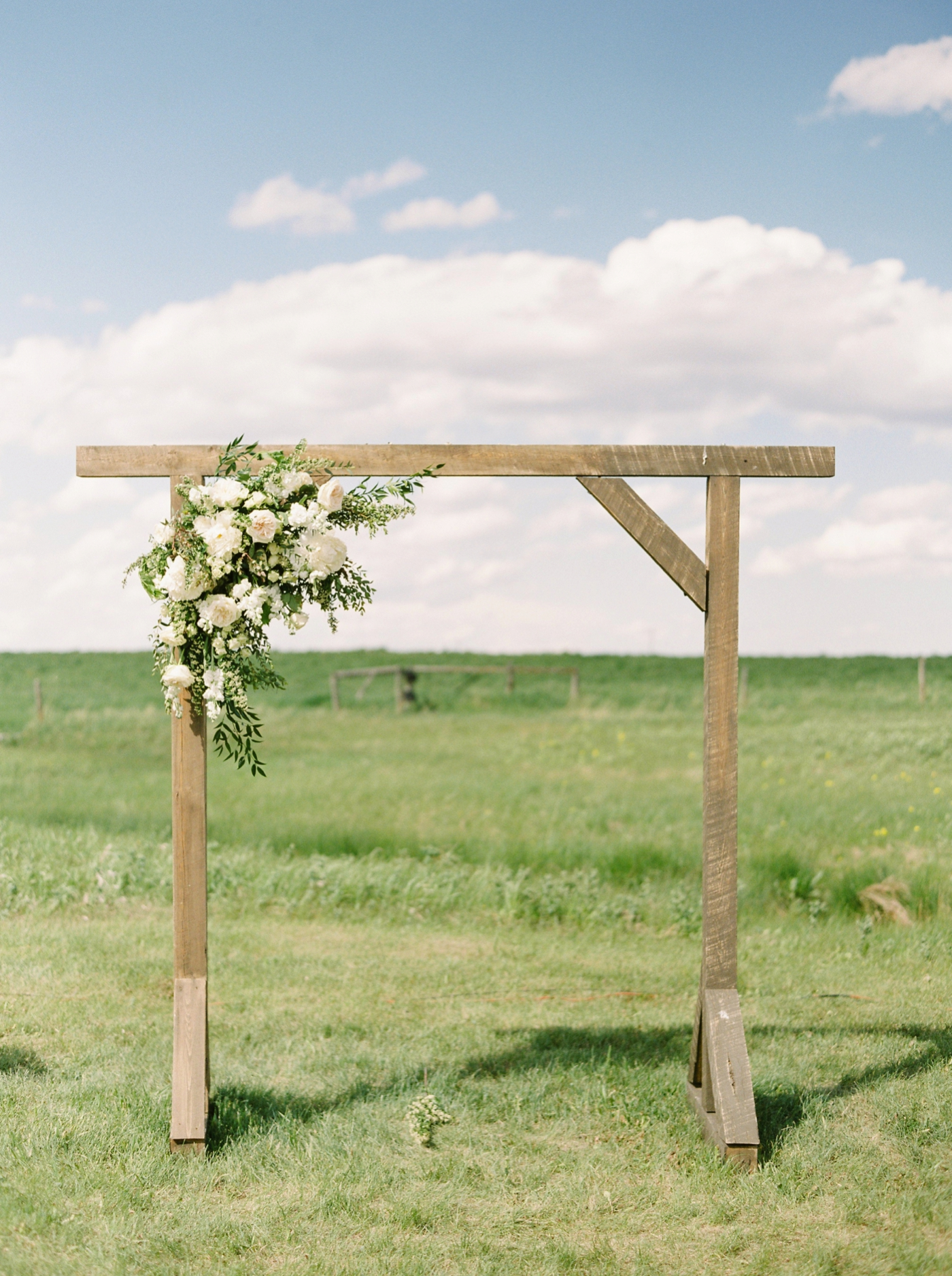 Calgary wedding photographers | The Gathered Farm Wedding | Justine milton fine art film photographer | outdoor farm wedding ceremony rustic arch structure