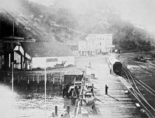"The Sausalito railroad and ferry wharf was a commercial hub in 1888. The sign on the barn at left center advertises an auction for ""Building Lots and Villa Sites."""