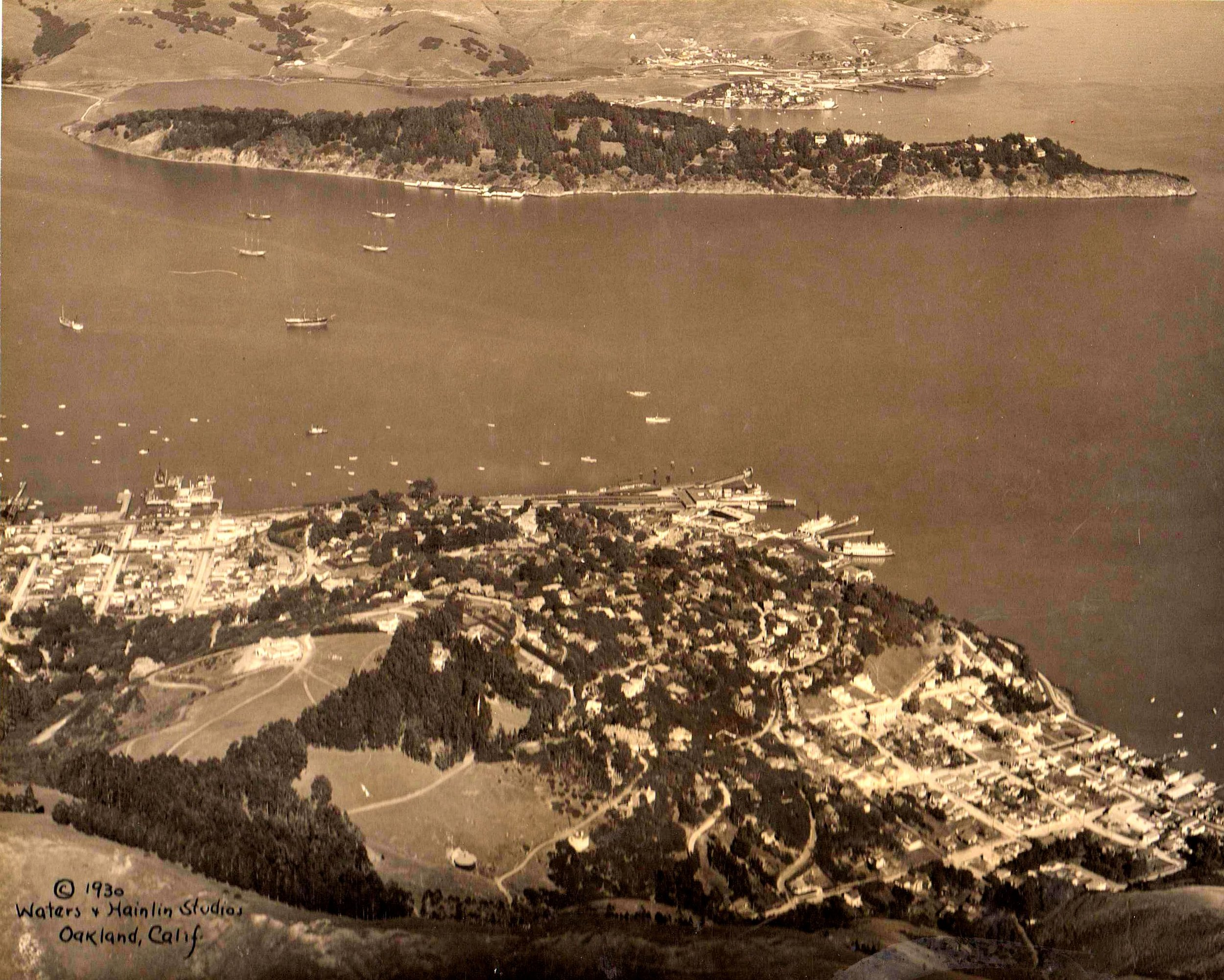PHOTO COURTESY OF SAUSALITO HISTORICAL SOCIETY  Sausalito in 1930, looking east from Wolfback Ridge. New Town is on the left, the Hill in the middle, and Old Town on the right. Both ferry systems are in operation.