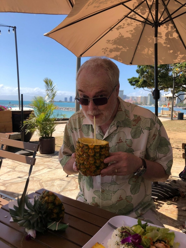 Ron enjoying a pineapple smoothie during a joint vacation with John and their families.