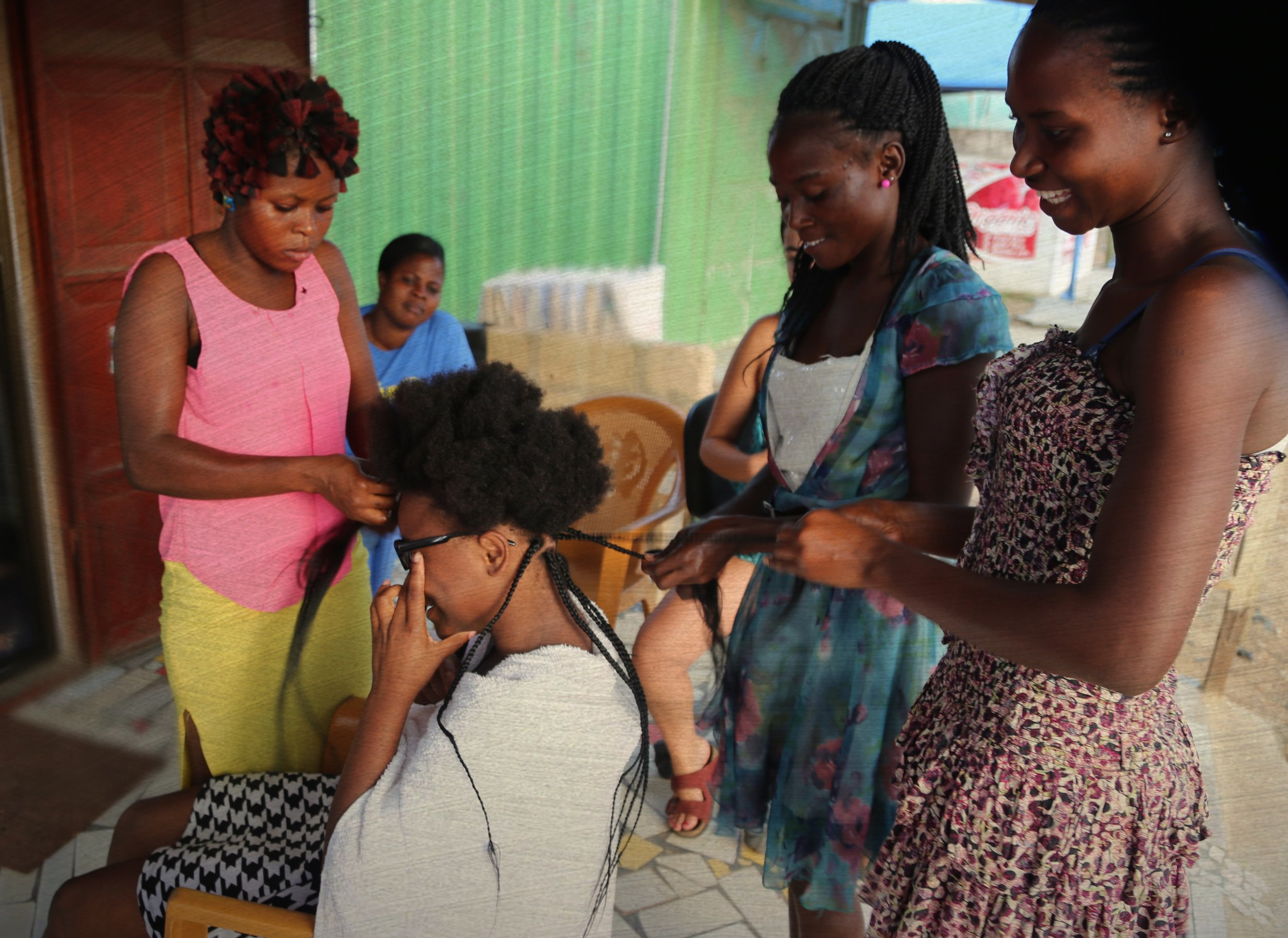 """Women in Ghana gather in friendship to do each other's hair, some much needed """"self care"""" that is often missing from their work-filled lives."""