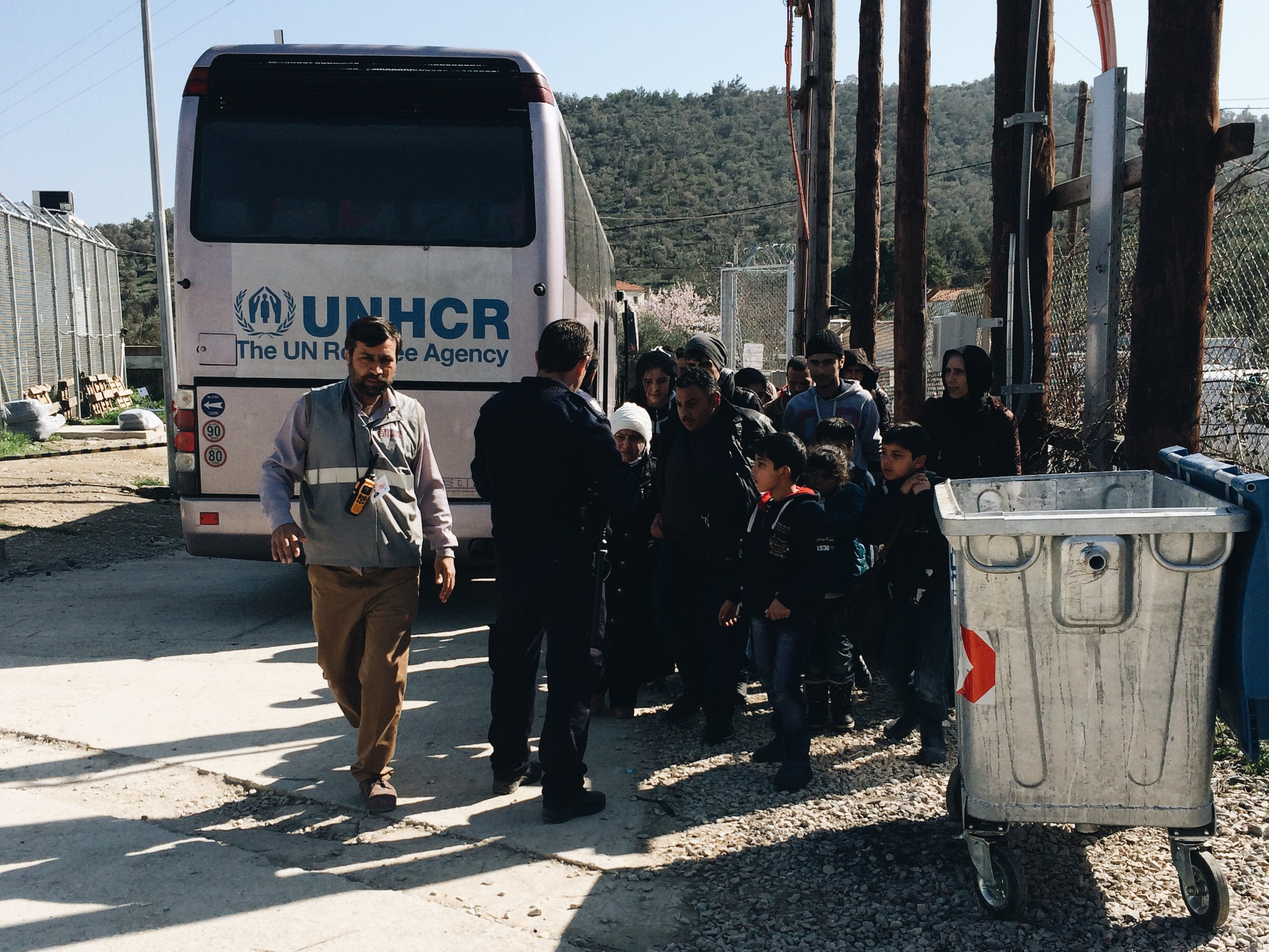 Refugees being received from UNHCR buses and given tickets with their registration numbers on them.