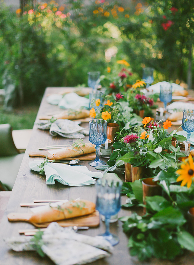 Photo:  Inspired by This    Here is another beautiful example of a Farm to Table themed tablescape - this one with perfect sized wooden cutting boards as the plates and a multitude of copper vases to hold brightly colored flowers and greenery is absolutely beautiful!