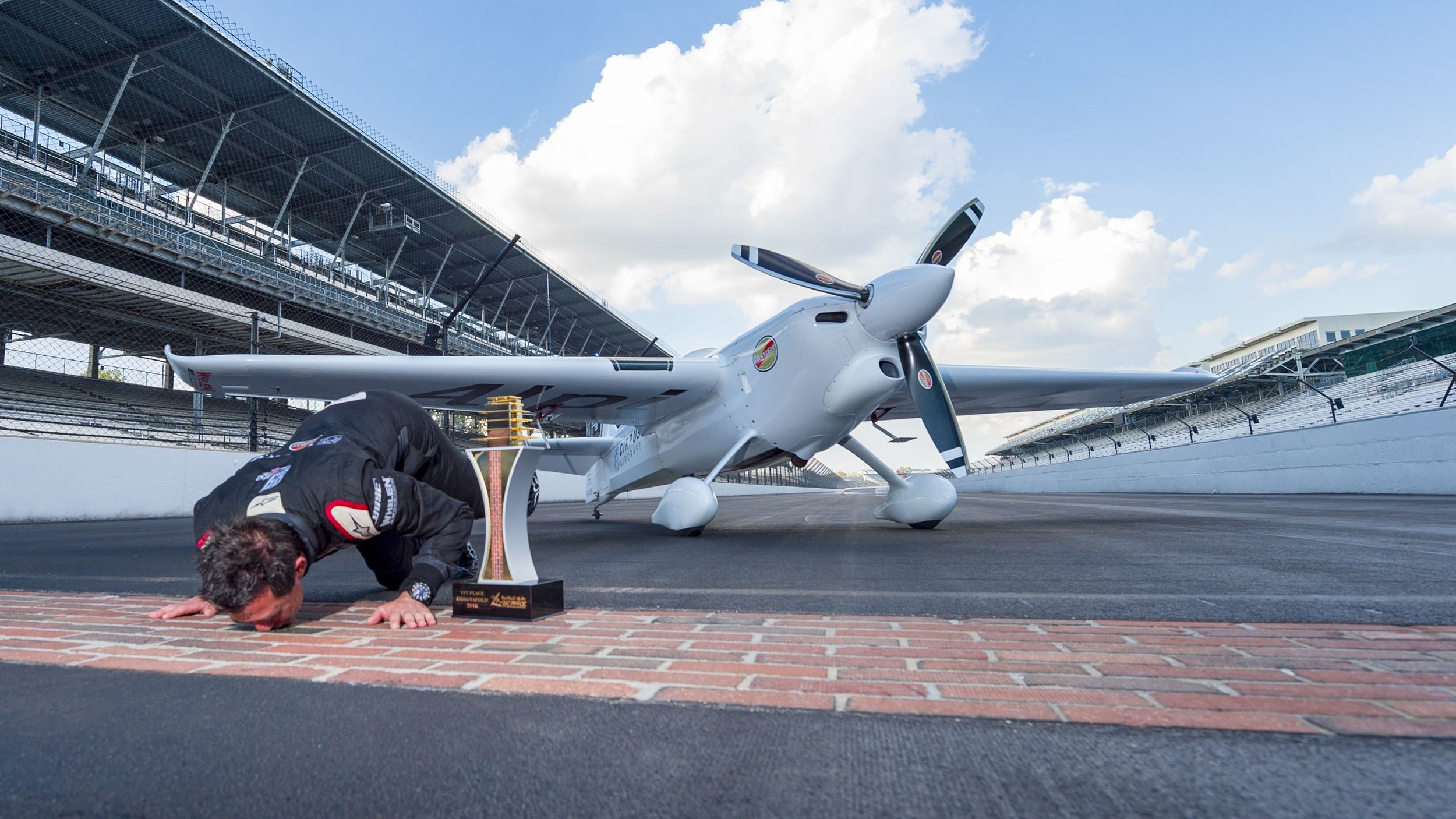 Michael Goulian kisses the bricks at Indianapolis Motor Speedway Following his Red Bull Air Race Win in late 2018.