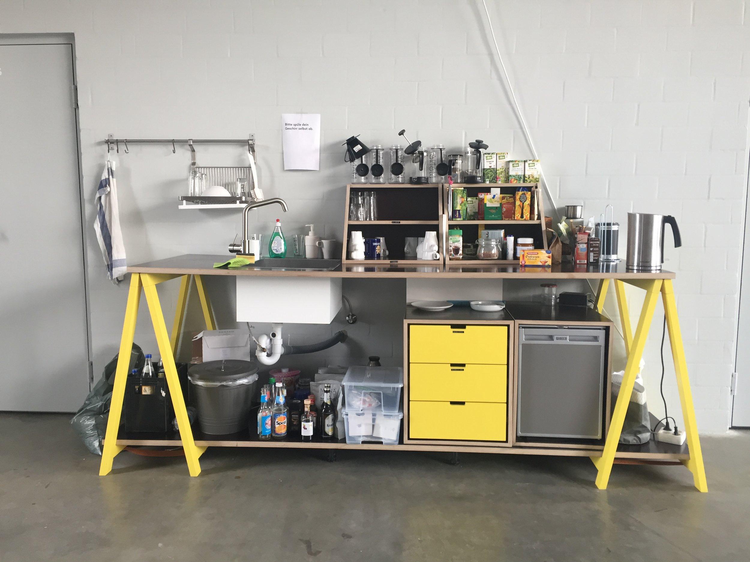Im Open-Space findest du eine gemeinschaftliche Teeküche mit Wasserkocher. Du kannst das Geschirr gerne nutzen, solltest es aber hinterher wieder abwaschen, Danke.
