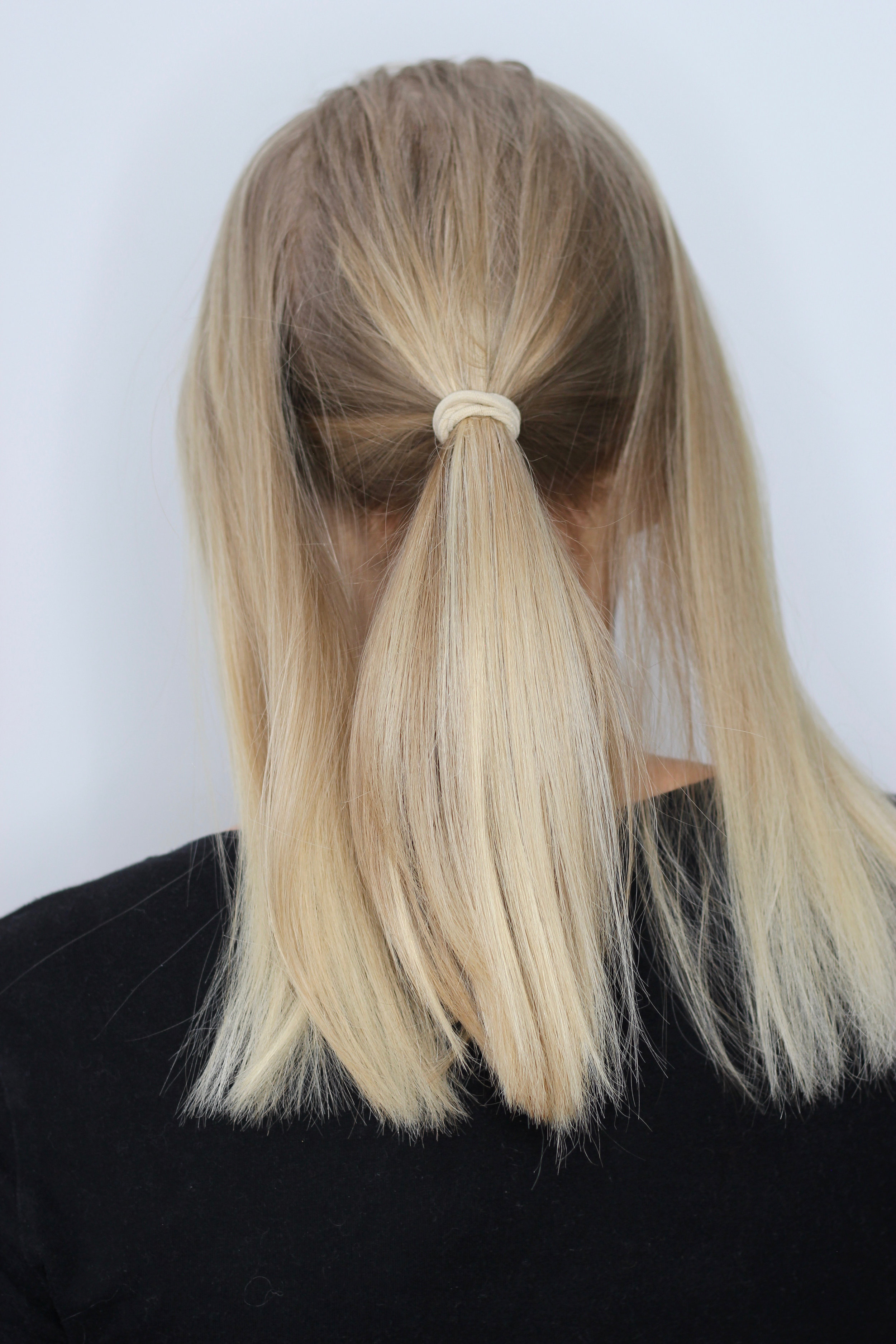 STEP 1 - Split your hair into 3 sections, with the middle section being the biggest one. Tie the middle section up into a low(ish) ponytail.