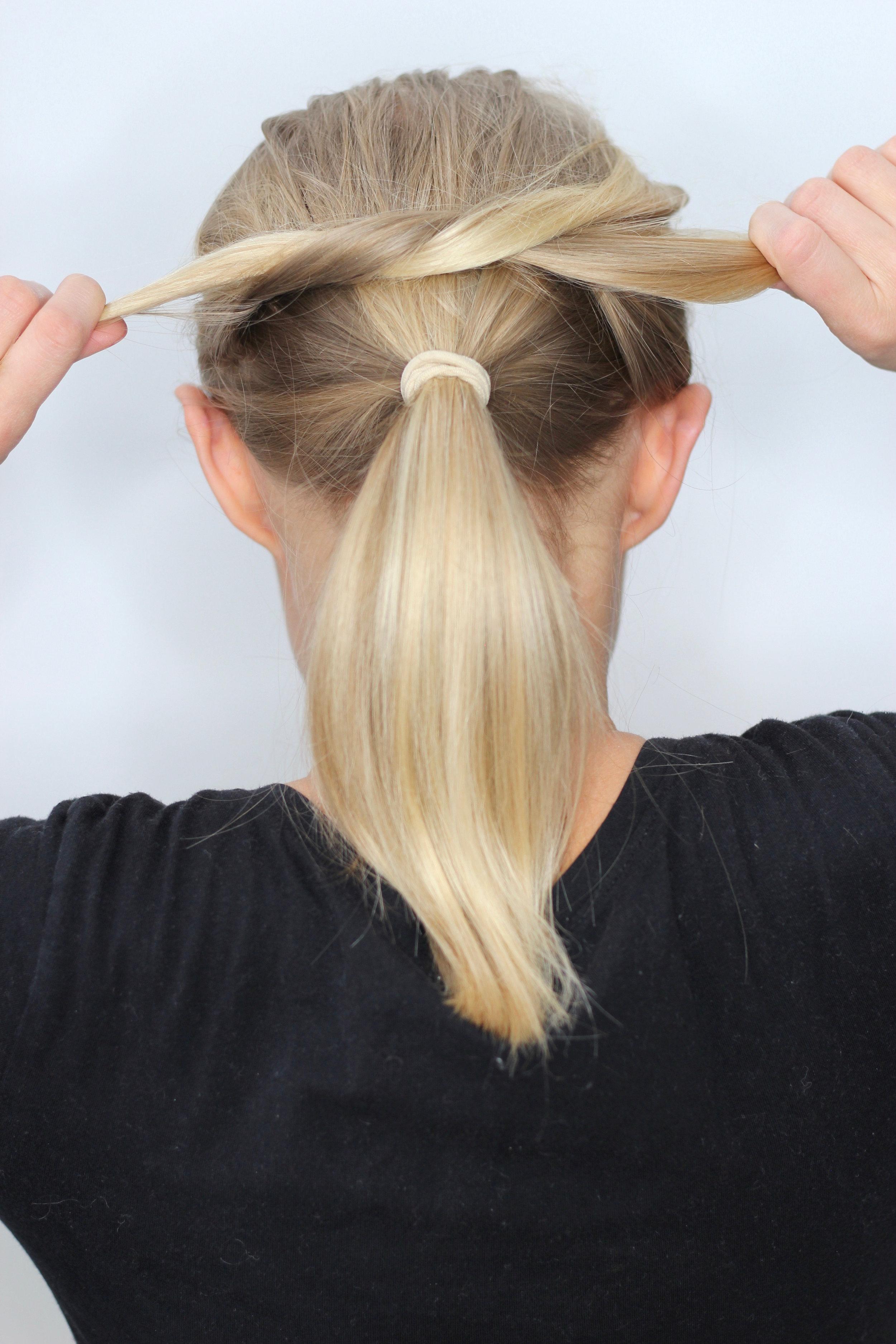 STEP 2 - Create a knot above the ponytail, using the two side sections.