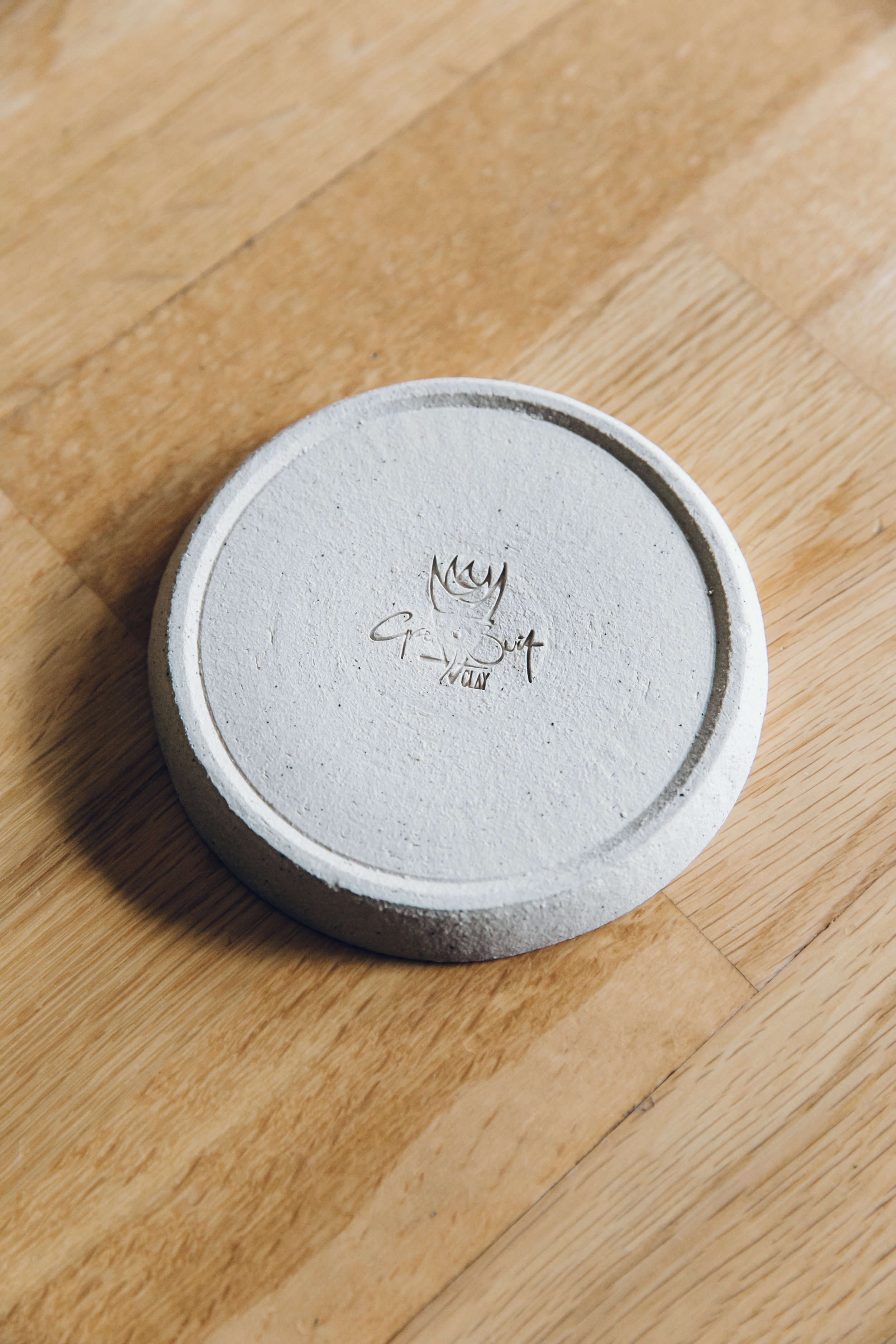 Grey suit Clay pottery logo
