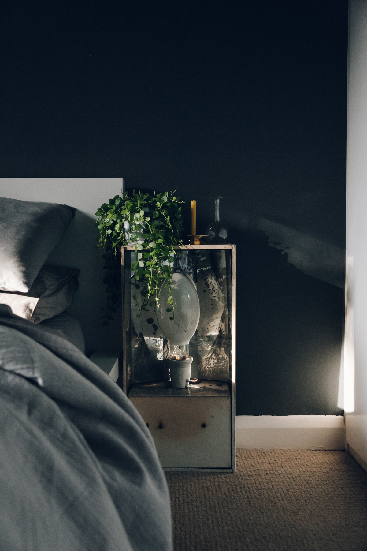 Bedside table with plants and candles.