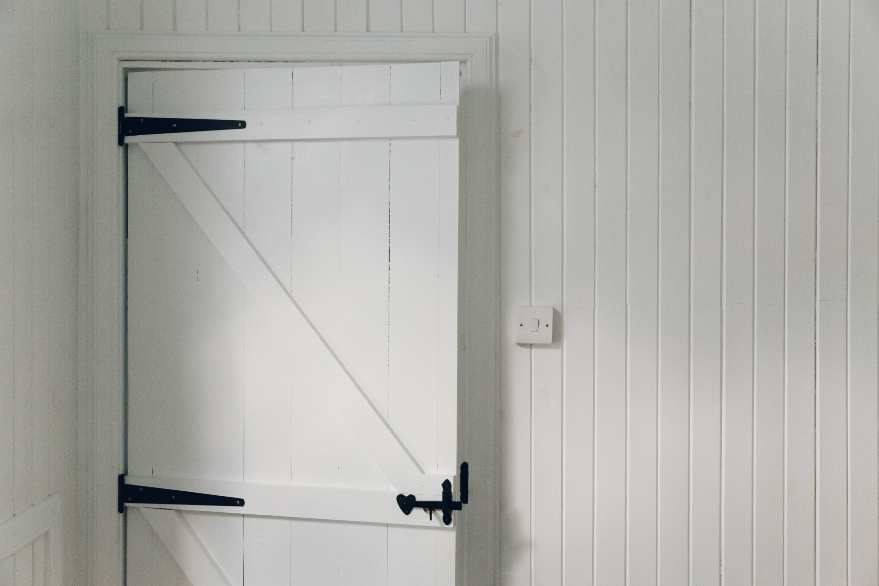 Painted white cladding inside the Scandinavian-inspired bedroom of The Crofter's House on the Isle of Skye.