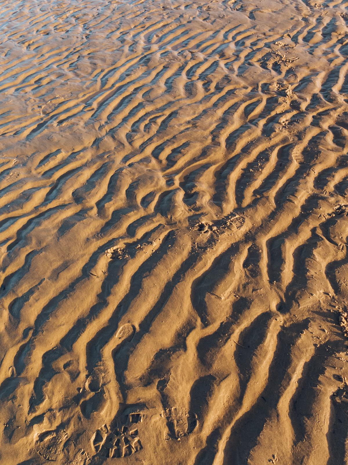 Light and shadow on a sandy beach.