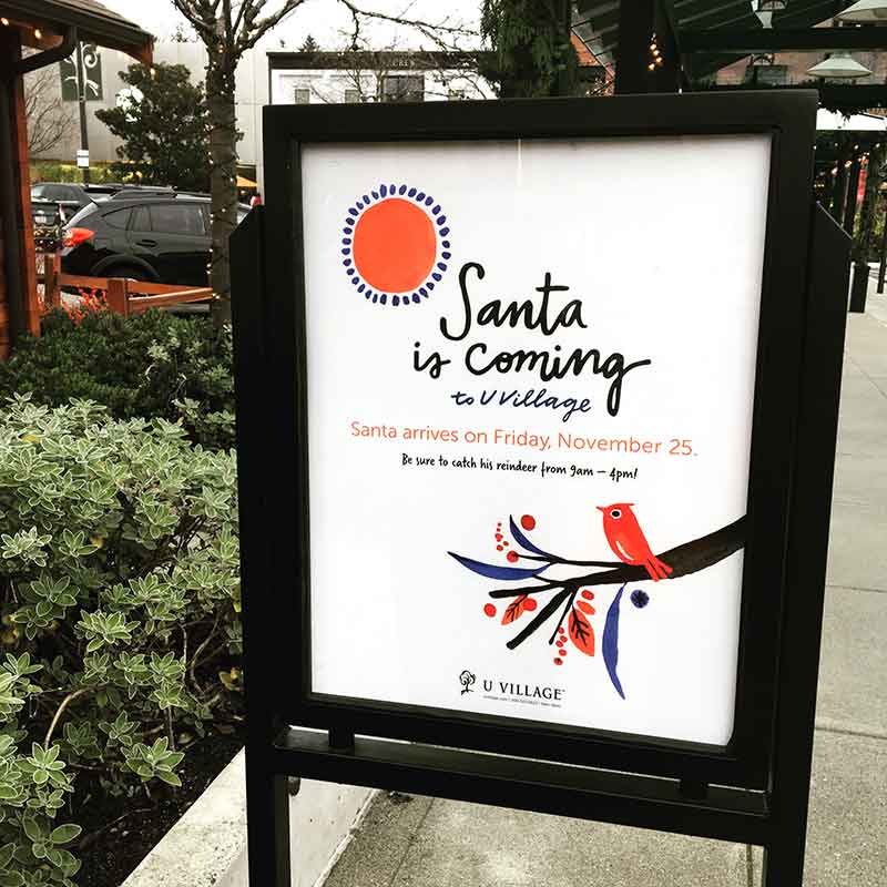 Misha Zadeh for University Village. On property promotional signage featuring vibrant watercolor illustrations.