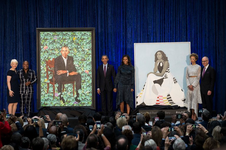 National Portrait Museum unveiled portraits of Barack and Michelle Obama on Feb.12nd, 2018. From Left to right, Kim Sajet, director of the National Portrait Gallery; Kehinde Wiley; President Barack Obama and Michelle Obama; Amy Sherald; David Skorton, secretary of the Smithsonian by The New York Times.