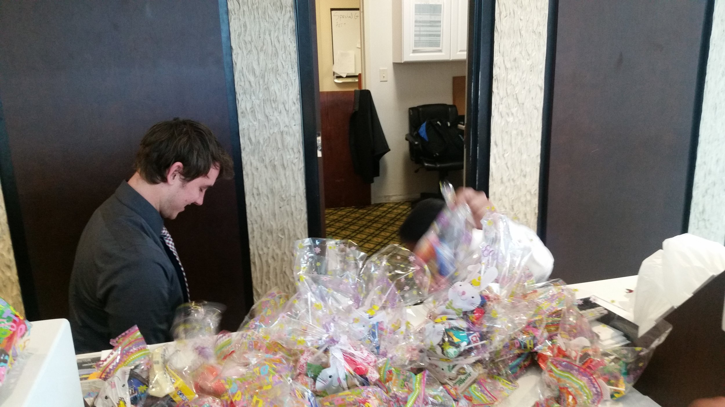 Front desk associate Nicholas getting all the candy bags ready to take to primary children's hospital .