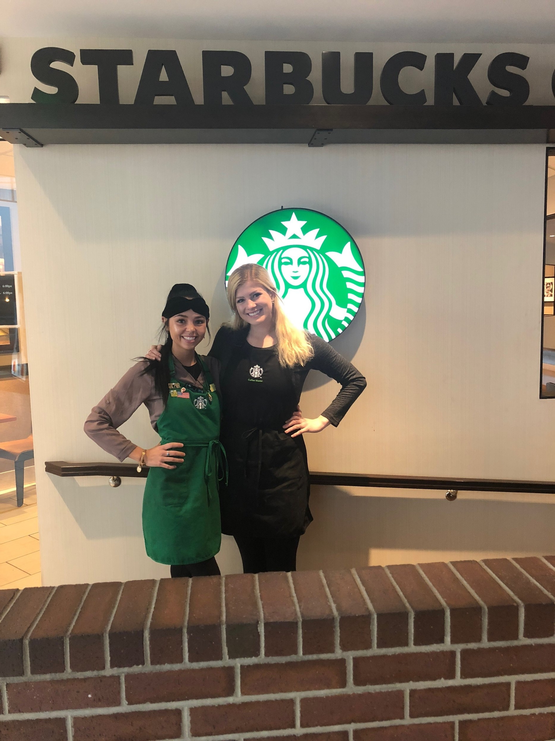 Starbucks manager Cait congratulating London on her promotion.