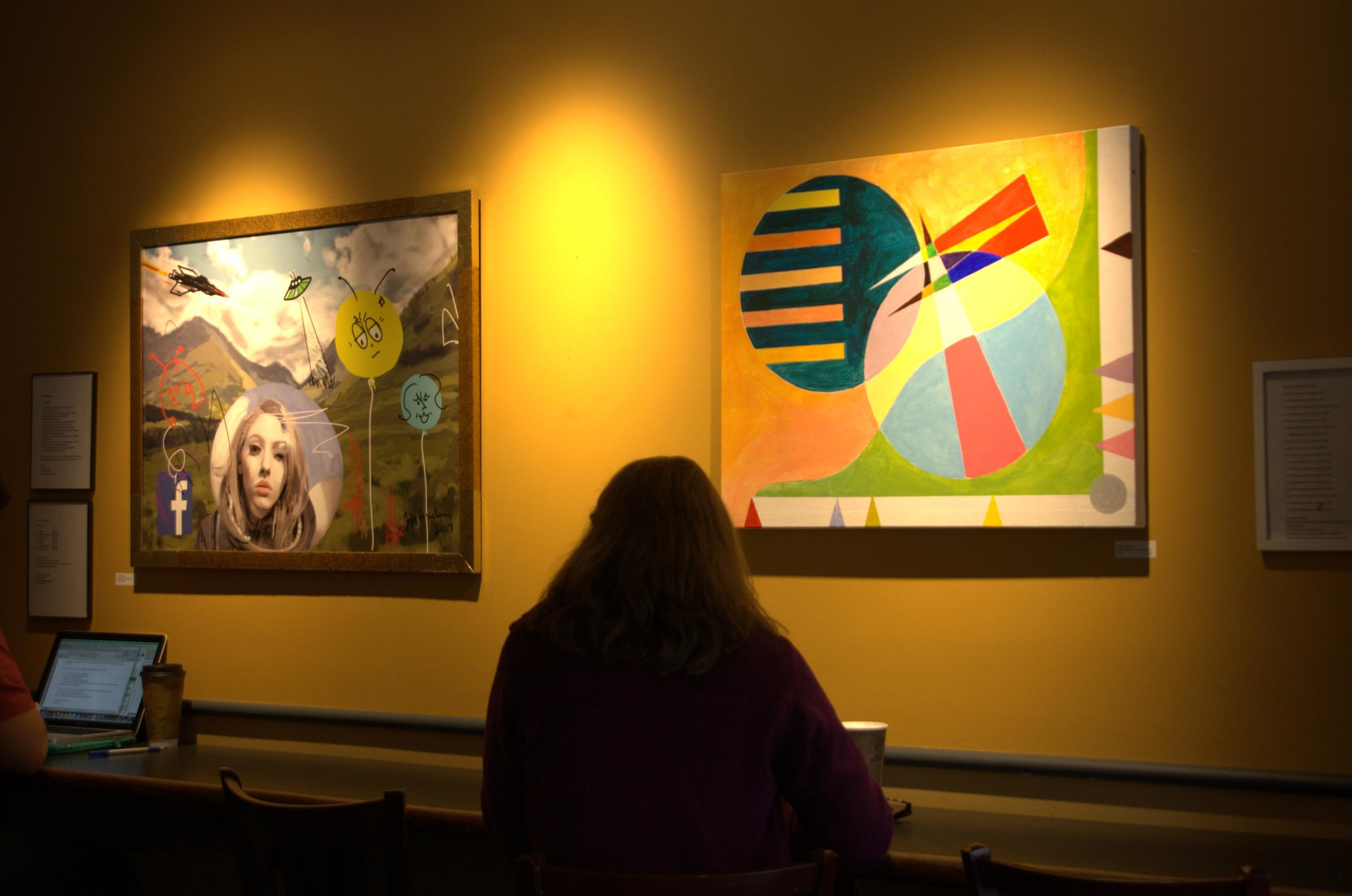 Jeff Hudson's 'Space Girl' painting, left, is displayed at Tunnel City Coffee next to his wife's acrylic painting on canvas titled 'Base.'