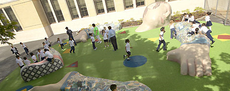 Youths play on the completed outdoor classroom and play structure in the form of a sleeping child.