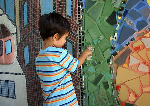 A child finds the tile he put on with his parent's help.