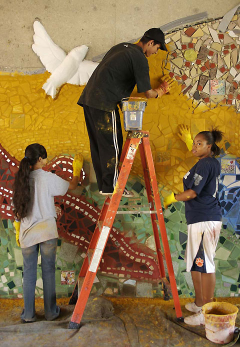 Youths complete the bricolage mosaic by grouting it.