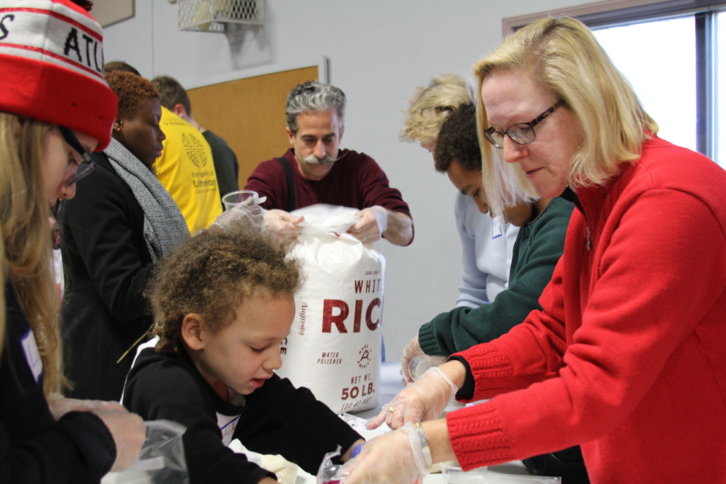 volunteers pack rice for refugees