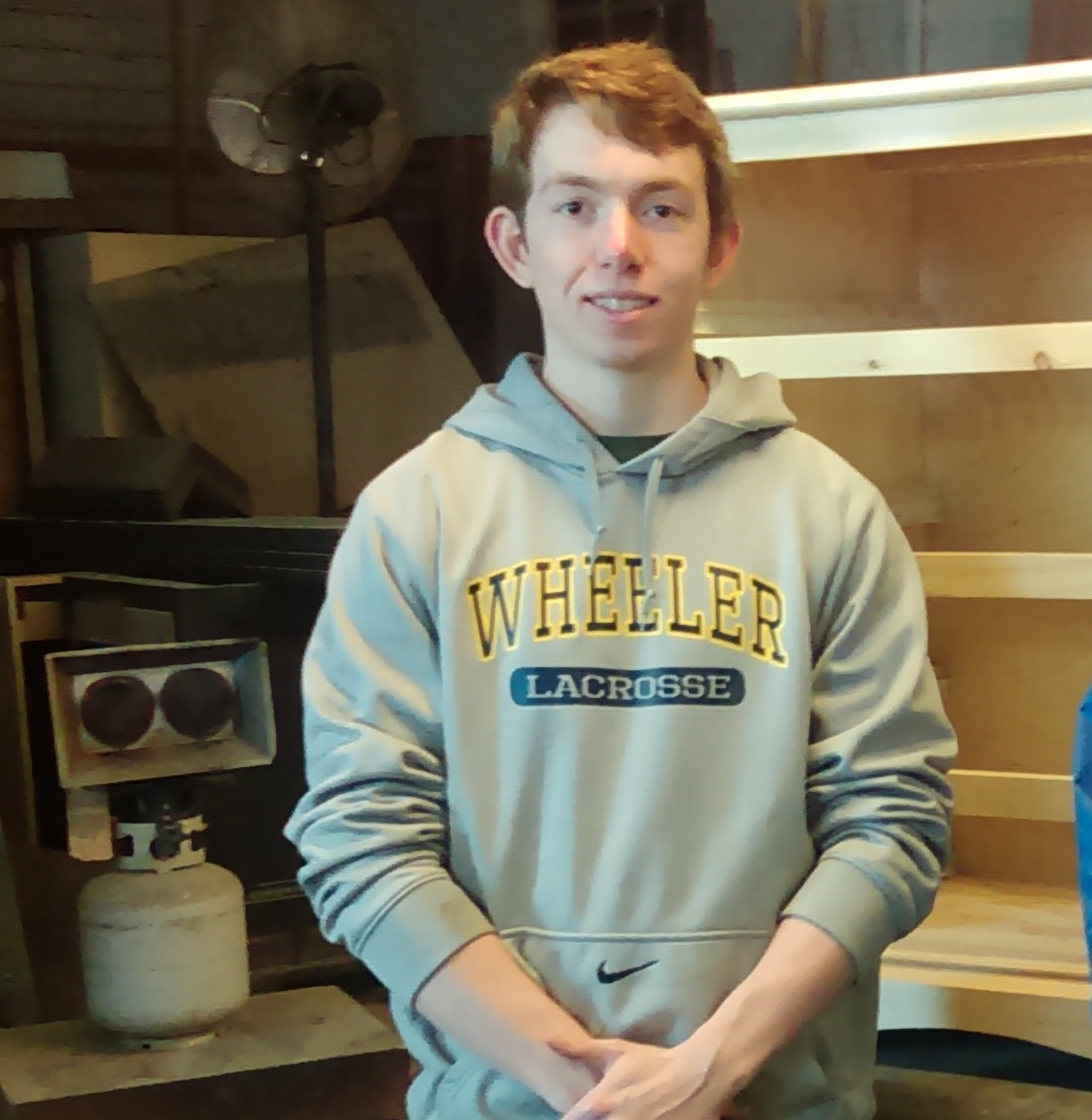 high school student with refugee woodworking project