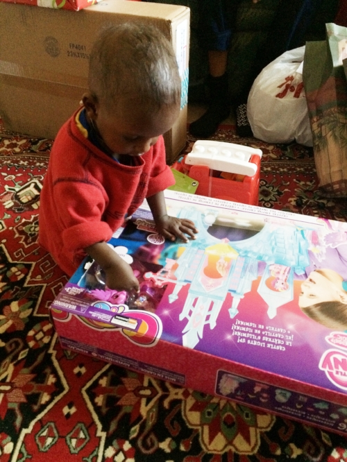 A young refugee boy opens a gift