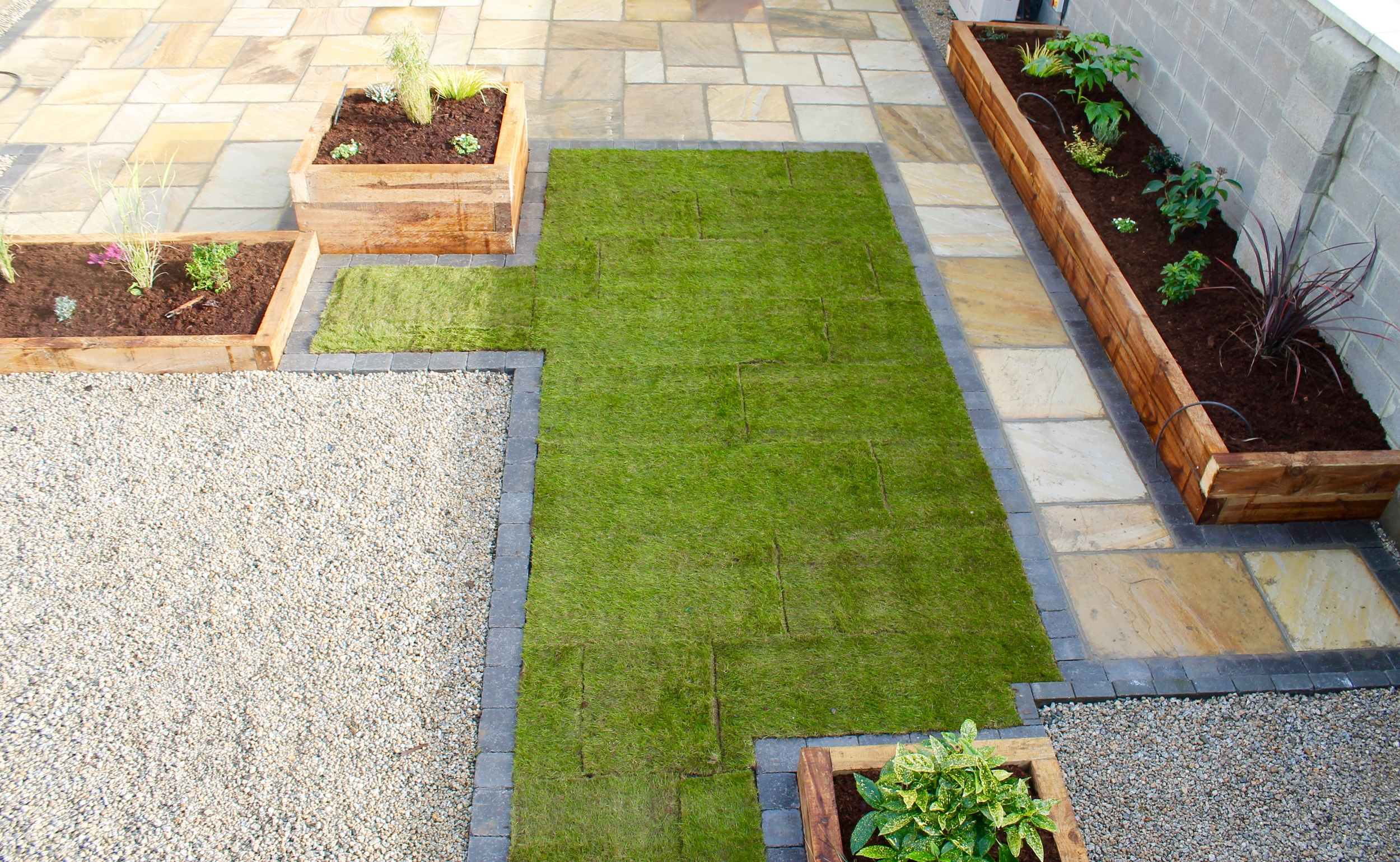 New Roll out Lawn with Carcoal brick edge,raised new sleeper beds with mood lighting and Sandstone Patio.