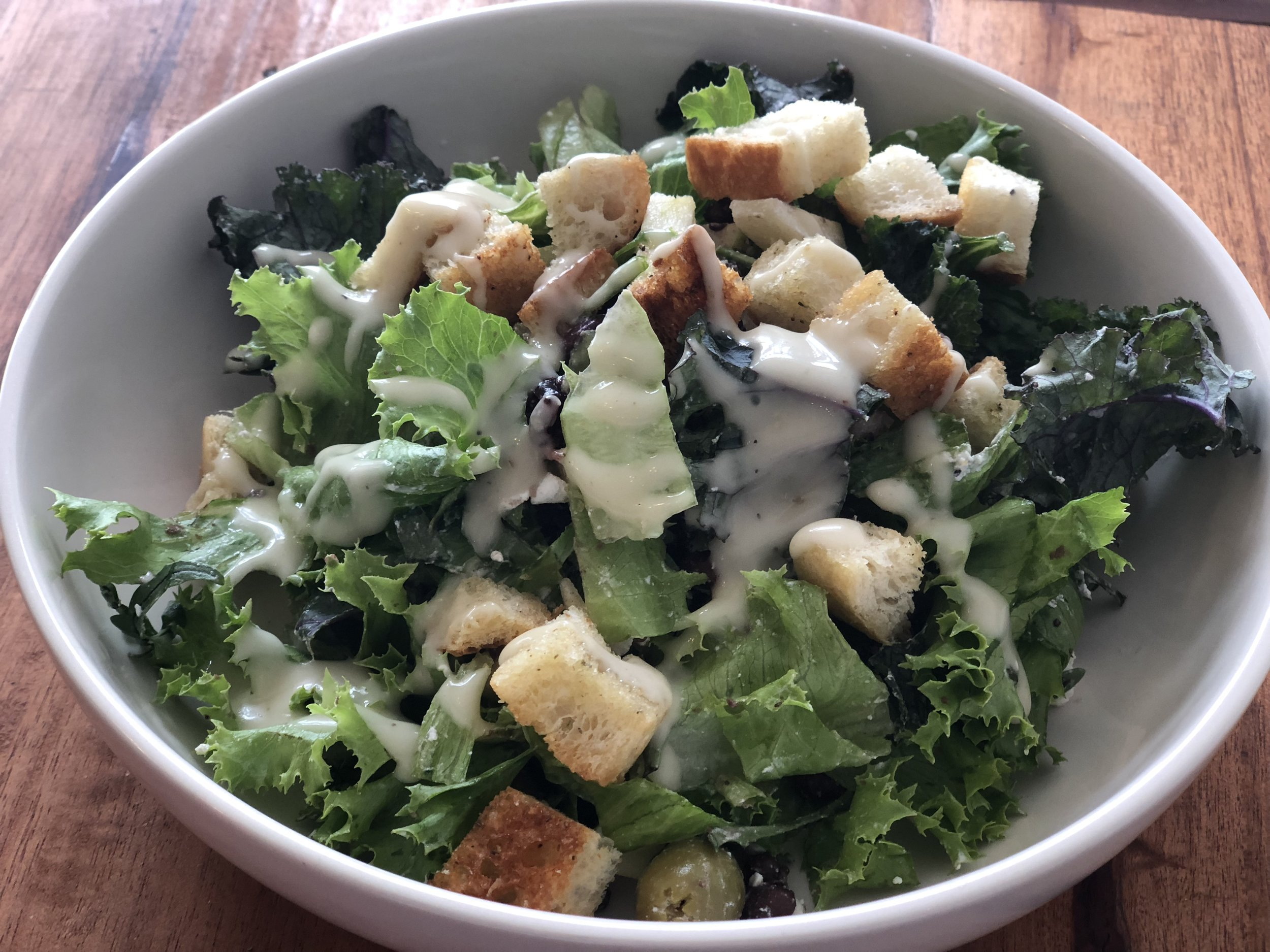 Mixed greens, Red beans, Olives, Apple, Raisins, Olives, Feta cheese, Croutons and a Caesar salad dressing