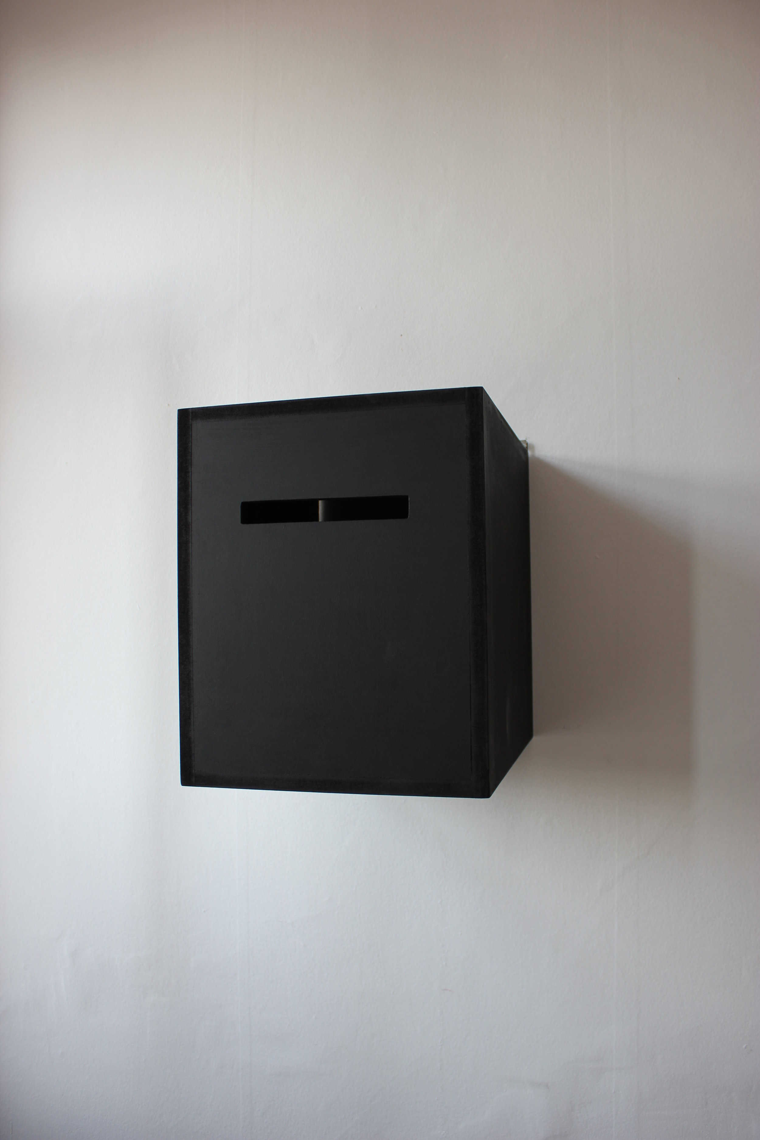 Box of smiling eyes, 2014.  31x38x40 cm  Closed painted wooden box with a small peephole to look inside the box and see your own eyes reflecting in a mirror and the word SMILE.
