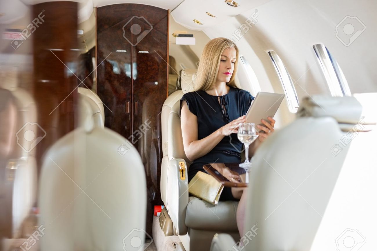 25762159-Rich-mid-adult-woman-using-tablet-computer-in-private-jet-Stock-Photo.jpg