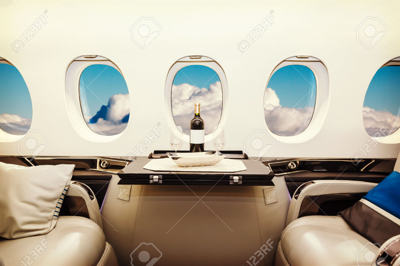 50871299-Luxury-interior-in-bright-colors-of-genuine-leather-in-the-business-jet-sky-and-clouds-through-the-p-Stock-Photo.jpg