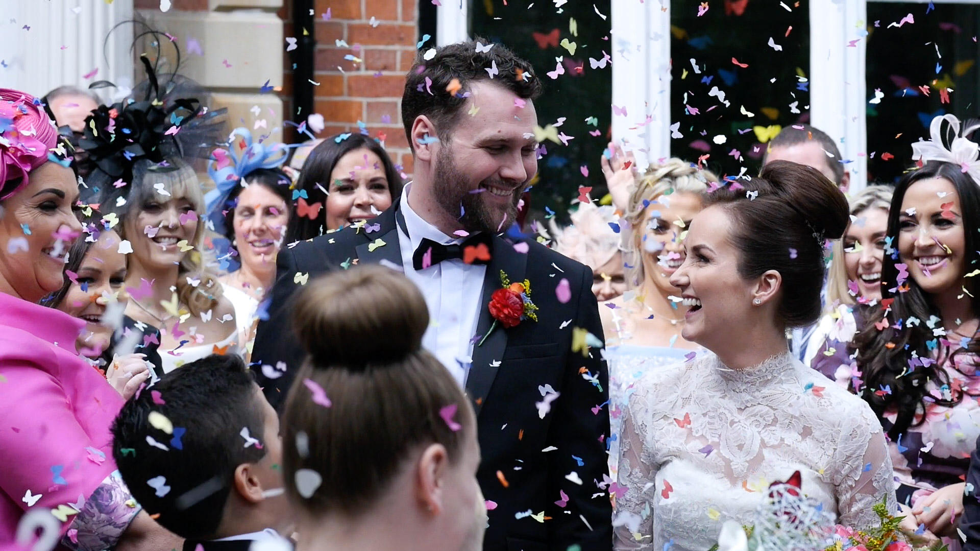 Jennifer and Luke smile at one another during the confetti short of their North West Wedding Video.