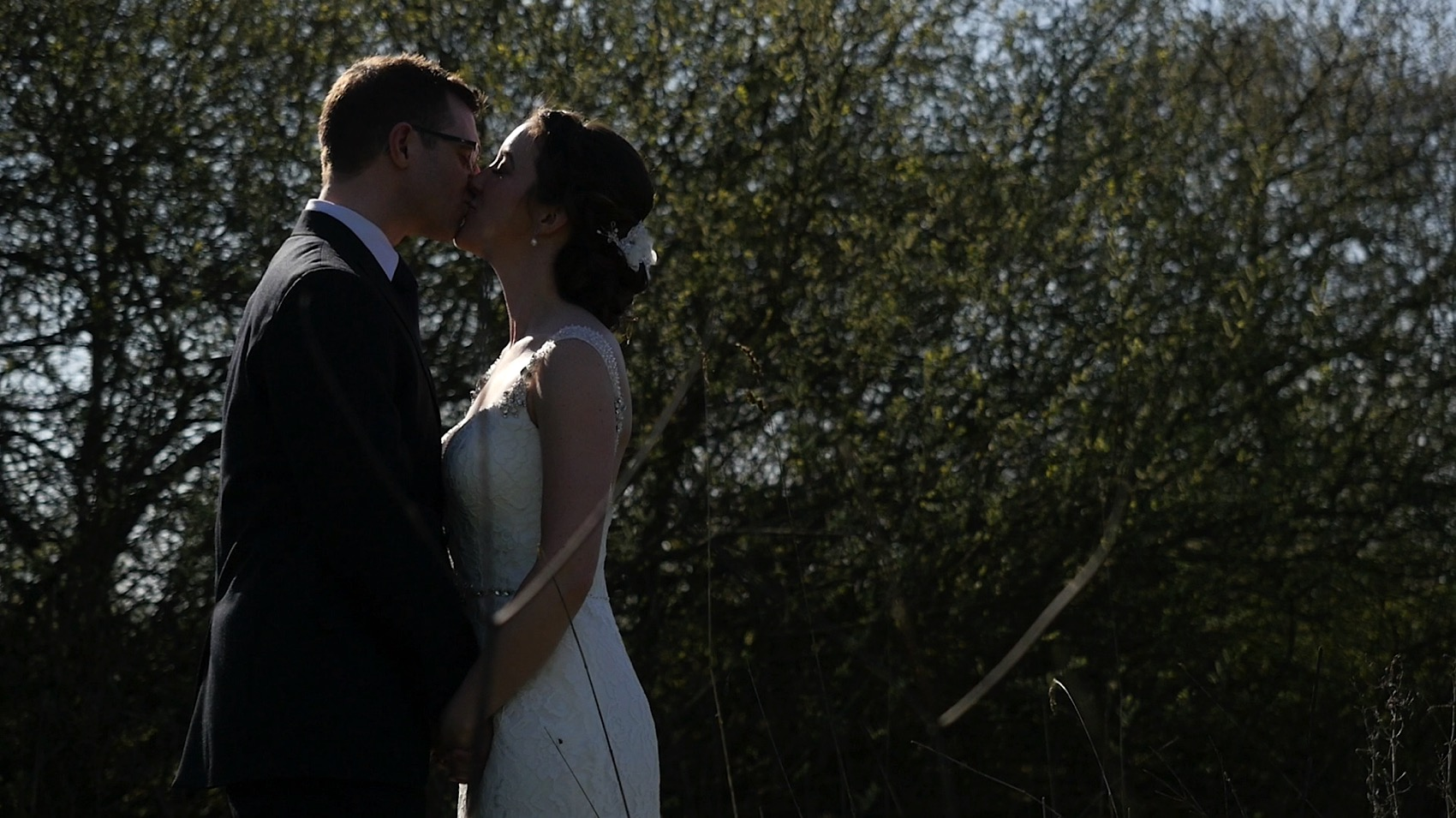 Tom and Laura share a kiss beside the lake at Styal Lodge during their Wedding Video.