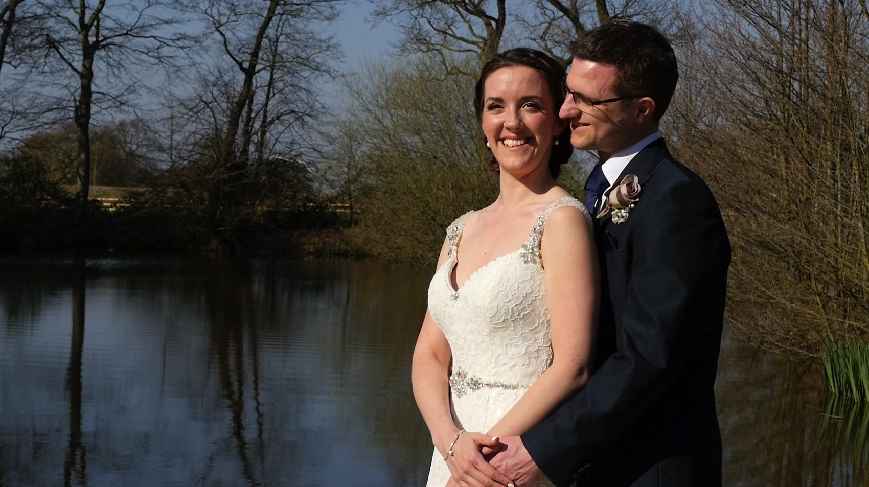 Tom and Laura pictured beside the lake during their North West Wedding Video at Styal Lodge.