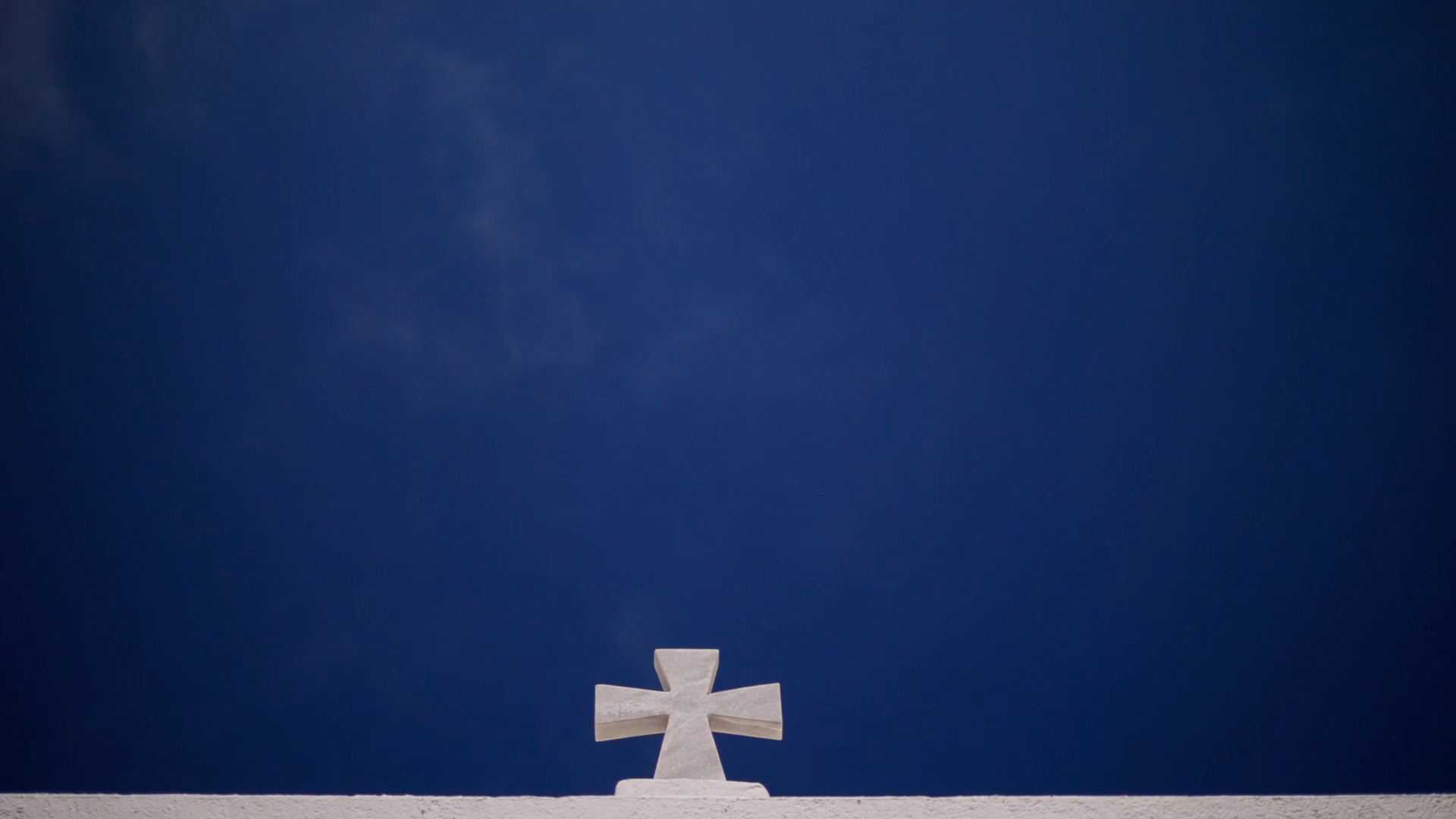 Santorini Wedding Videographer visits Santorini - shot shows church cross at the bottom of the frame with a luminous blue sky above, filling the rest of the frame.
