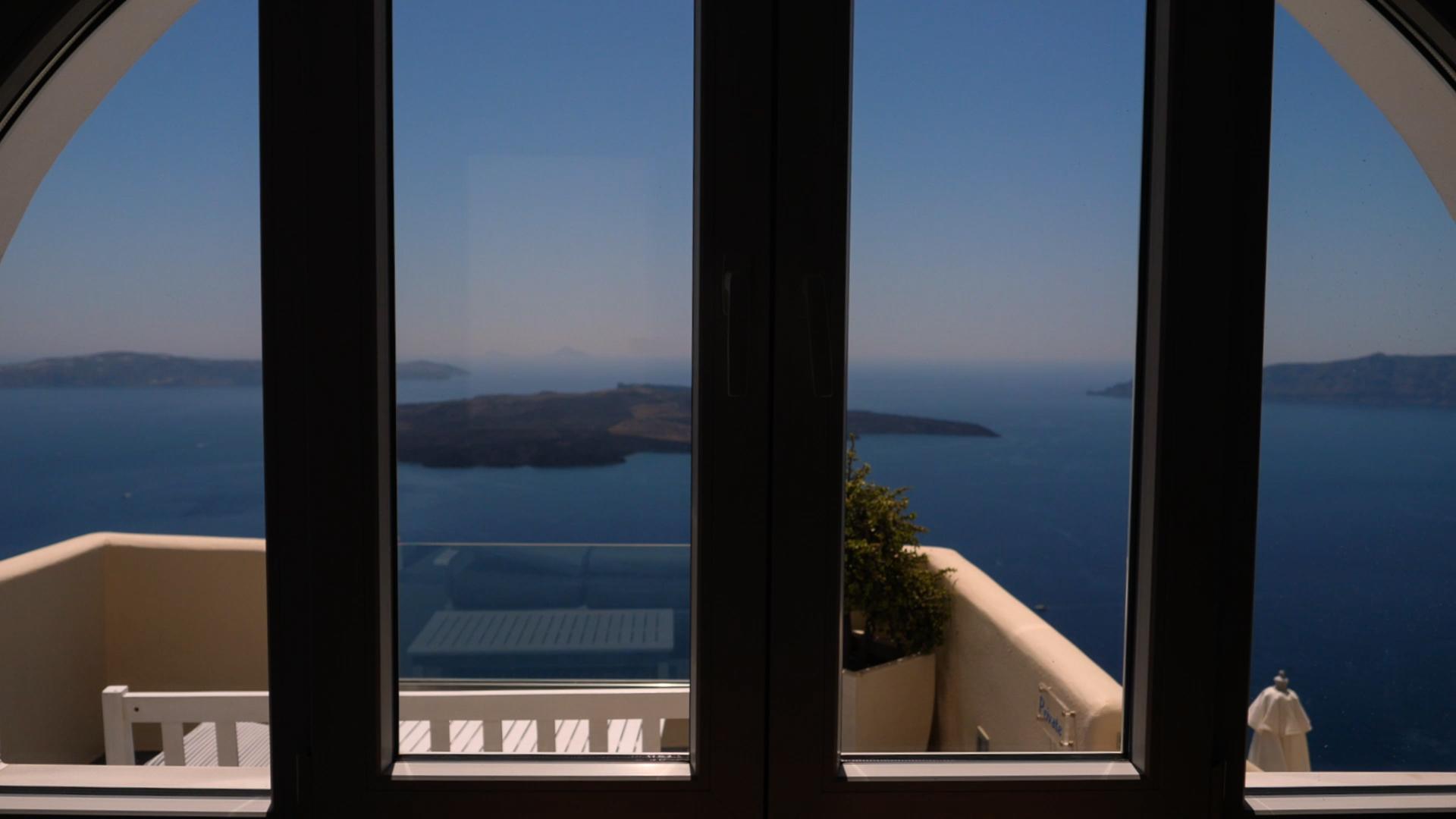 Santorini Wedding Videographer captures stunning view of the Caldera through groom's window.