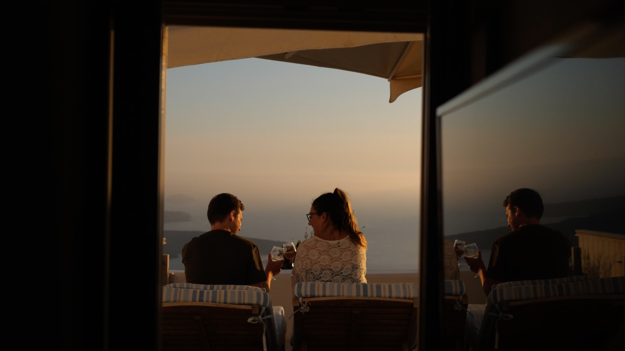Sara and Gareth say cheers to one another, whilst overlooking the beautiful sunset of Santorini's Caldera.
