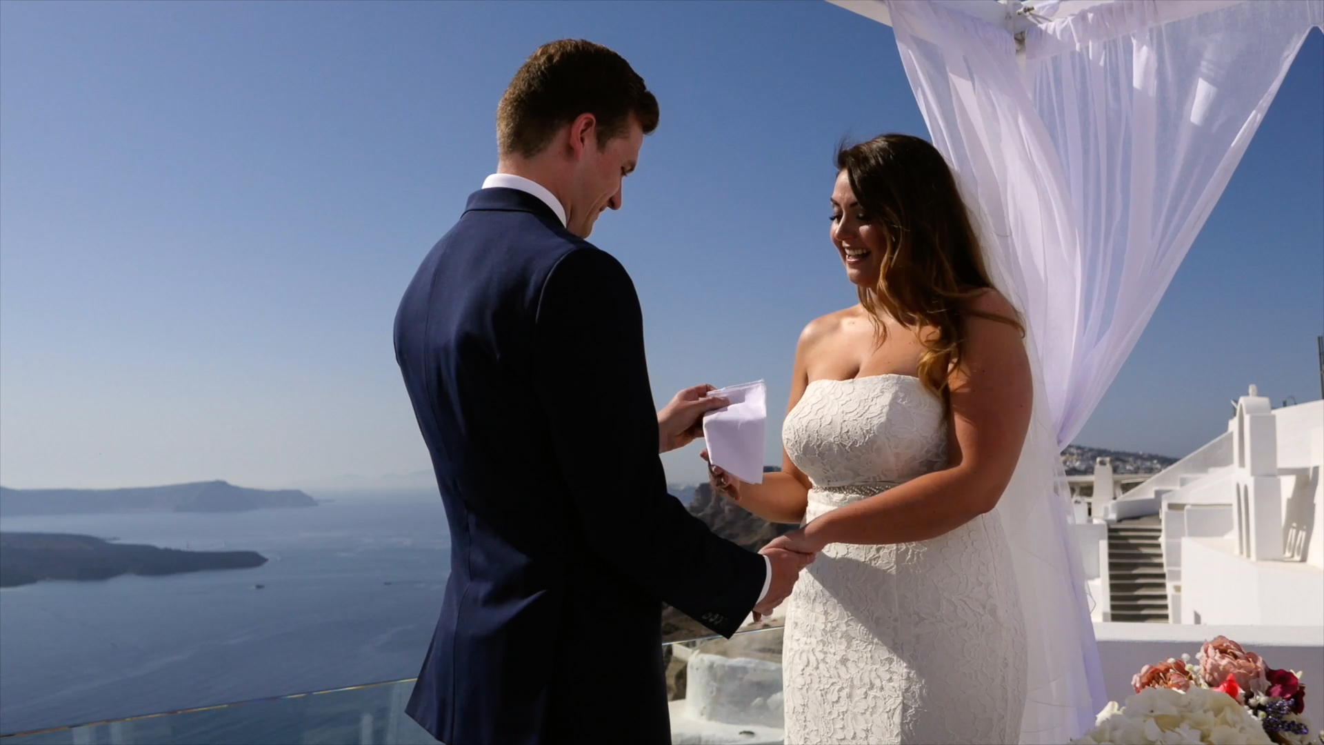 Santorini Wedding Videographer captures crying bride, as her groom places a tissue in her hand from his top pocket.