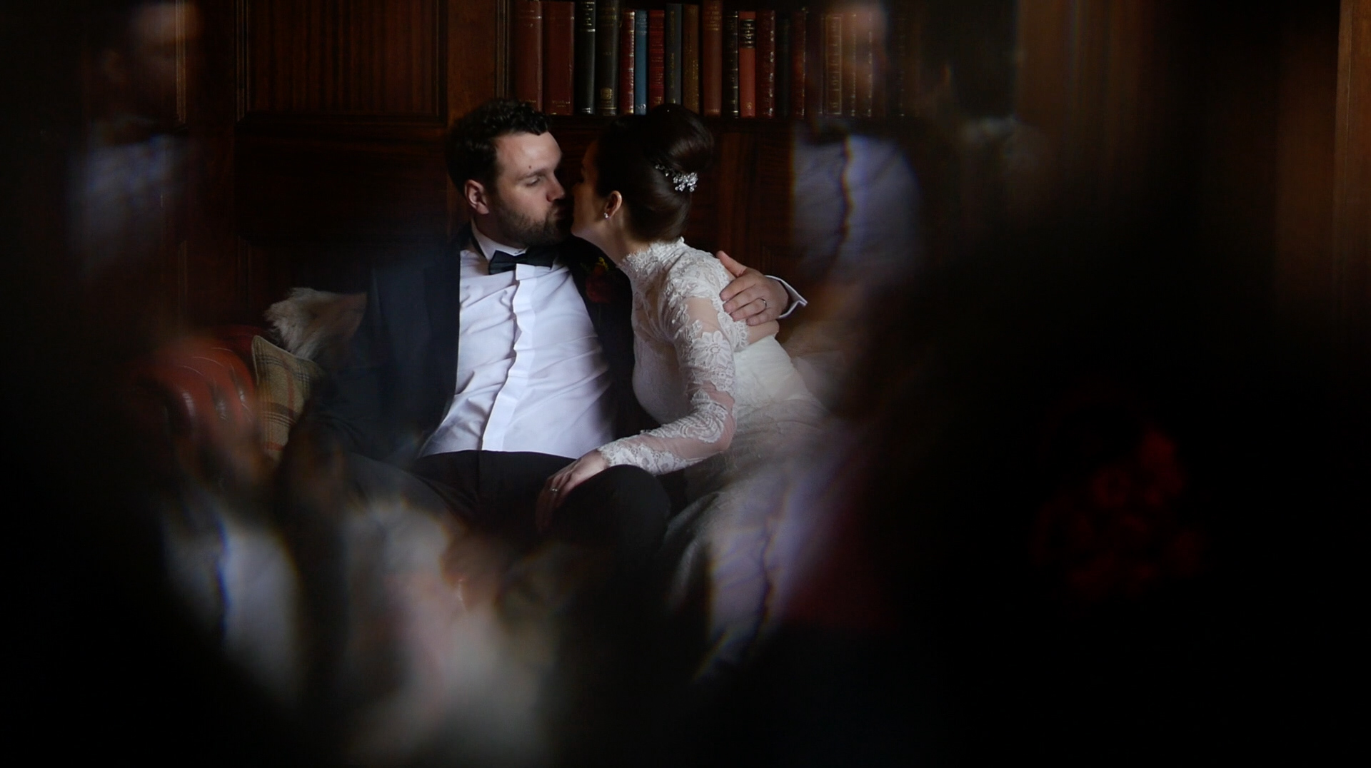 Jennifer Sandra Ginley and Luke share a kiss on their wedding day whilst sitting on a couch together at the stunning, Ashfield House wedding venue.