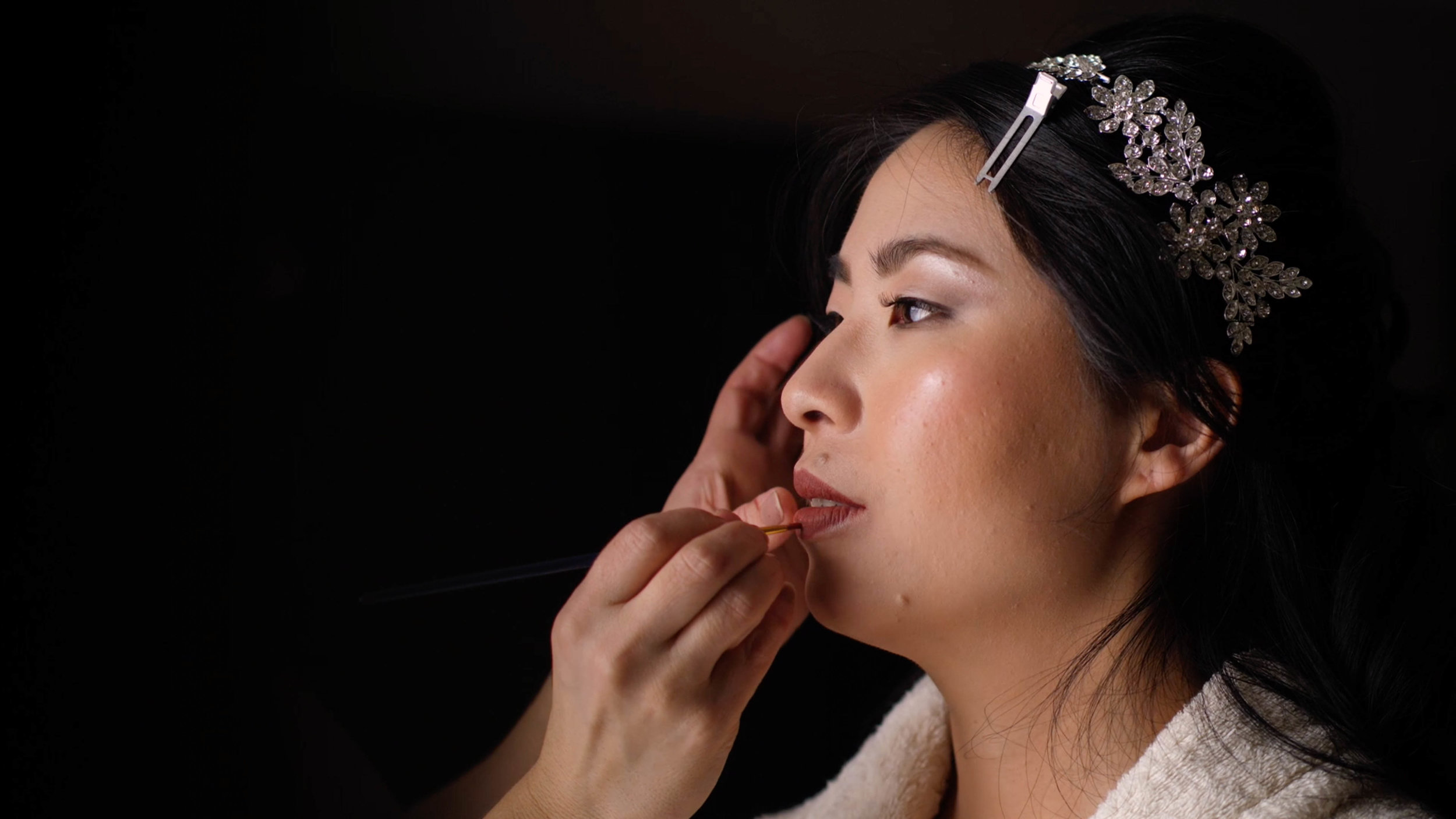 Bride getting ready for her wedding day by placing lipstick on her lips underneath beautiful window light.